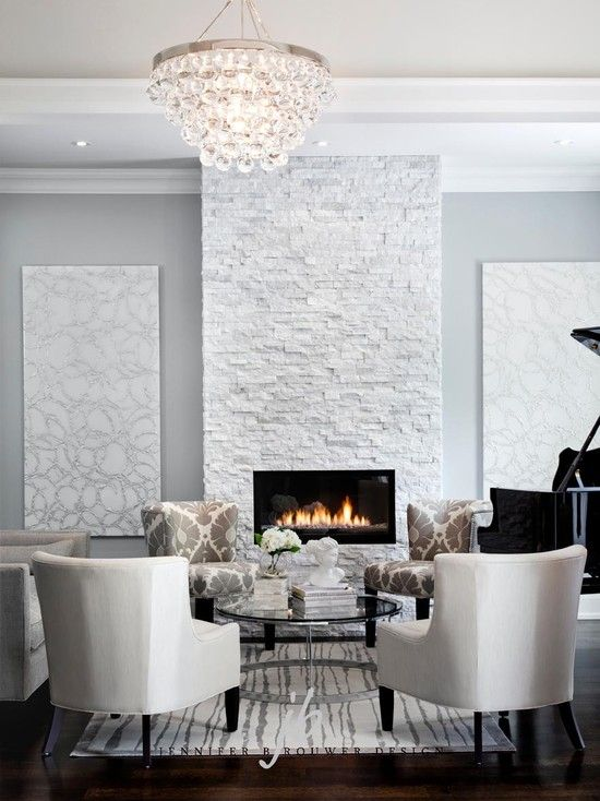 Living room with natural stone fireplace white and grey colors contemporary art white seating round glass coffee table wood ceiling mouldings baby grand piano books boxs accessorizing a table top accessories dark wood floors.jpg