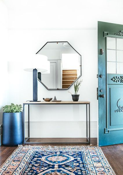 Small entry space but big impact thru color repeated in the are rug and door. Rustic and modern touches add warmth. The geometric mirror opens up the space and is very functional at the same time.
