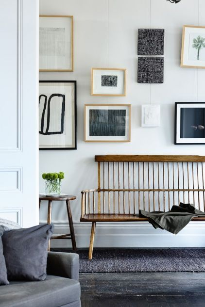 A simple vintage farm bench seat with clean modern white walls. Contemporary Art juxtaposes with the wood seating and as usual always make a space interesting to look at.