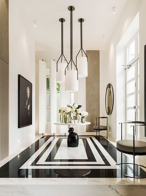 High Contrast is always a winner when it comes to make a space dramatic. Beautiful art as a focal point and a lot of geometric elements in the black and white marble patterned floor and the wood slatting in the wall and console table.