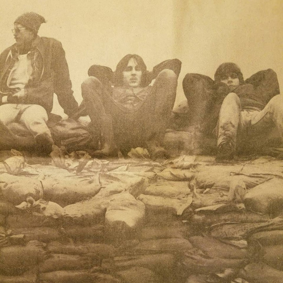 Three sandbaggers along the Pemberton dike by John Stearns of  The News-Sentinel .