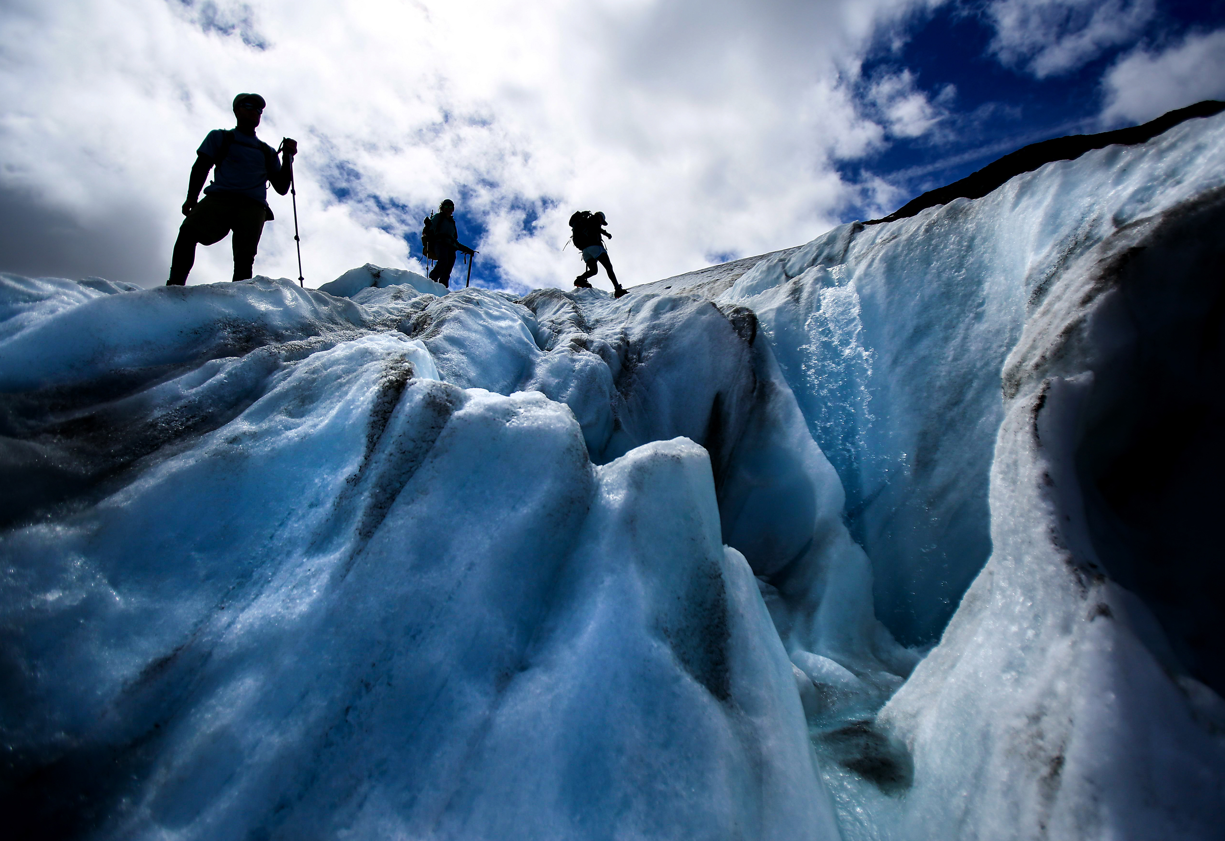 Research assistants navigate around a supraglacial stream on Mt. Baker's Sholes Glacier as they make measurements to assess the volume lost that will be added to the 32 years of data recorded by Glaciologist Mauri Pelto, Friday, Aug. 7, 2015. The glacier has receded over 90 meters, said Pelto. (Sy Bean / The Seattle Times)