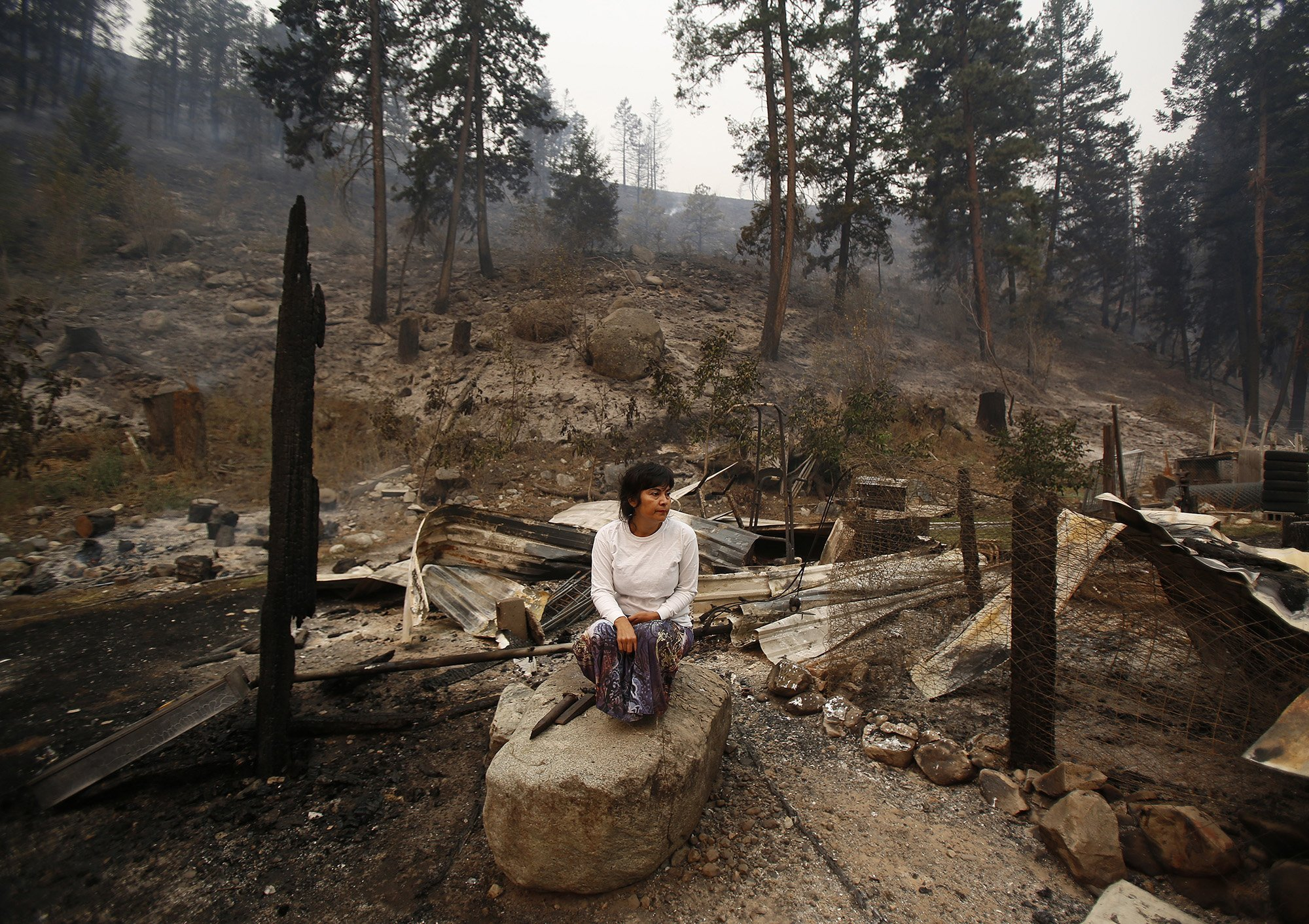 Sandra Gomez sits on amongst the rubble of her home of 30 years that was taken by the fire storm that swept through Antoine Creek the night before, on Saturday, Aug. 15, 2015.