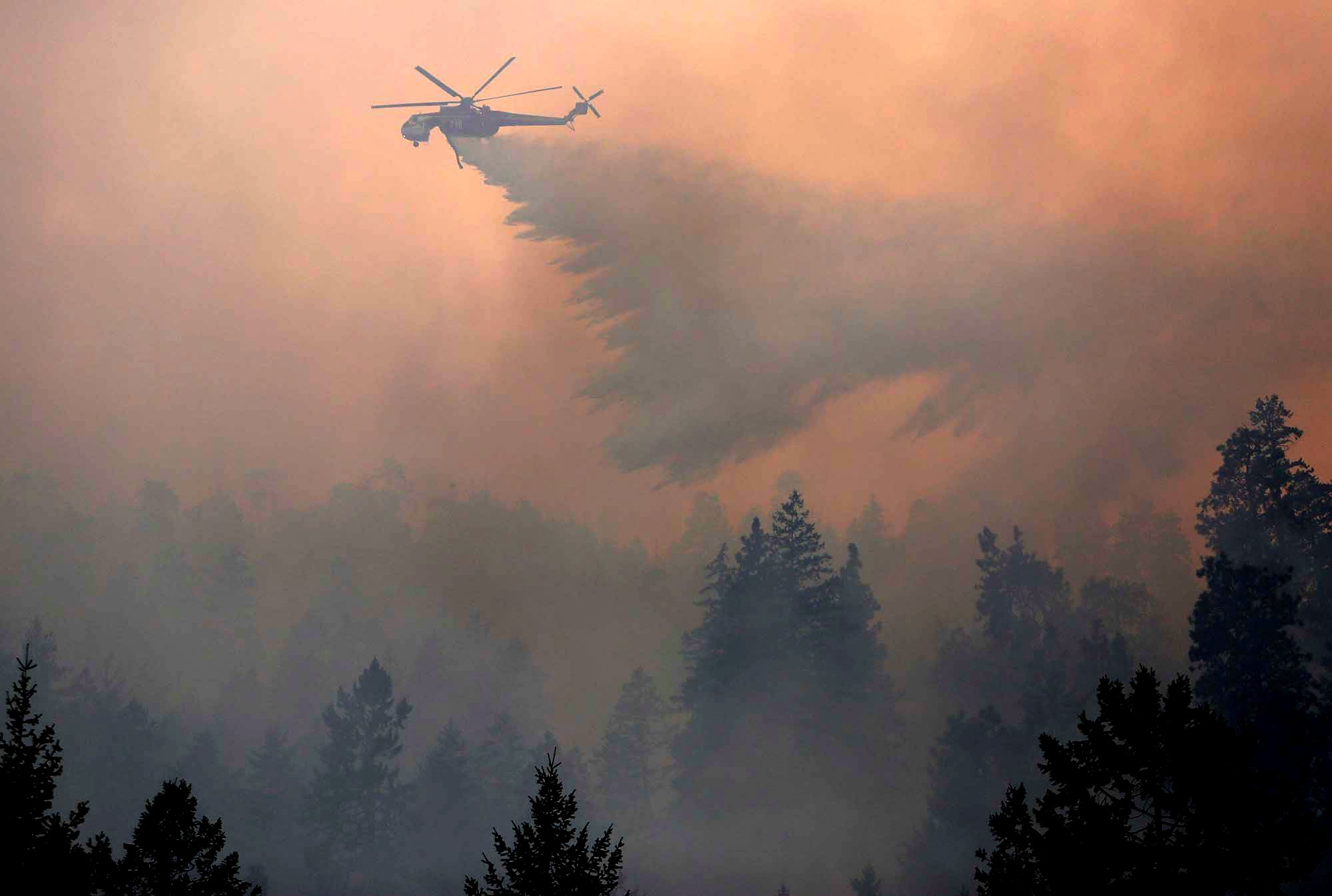 An Erikson Sky Crane drops a load of water on the First Creek Fire in the Lake Chelan State Park on Sunday, Aug. 16, 2015.
