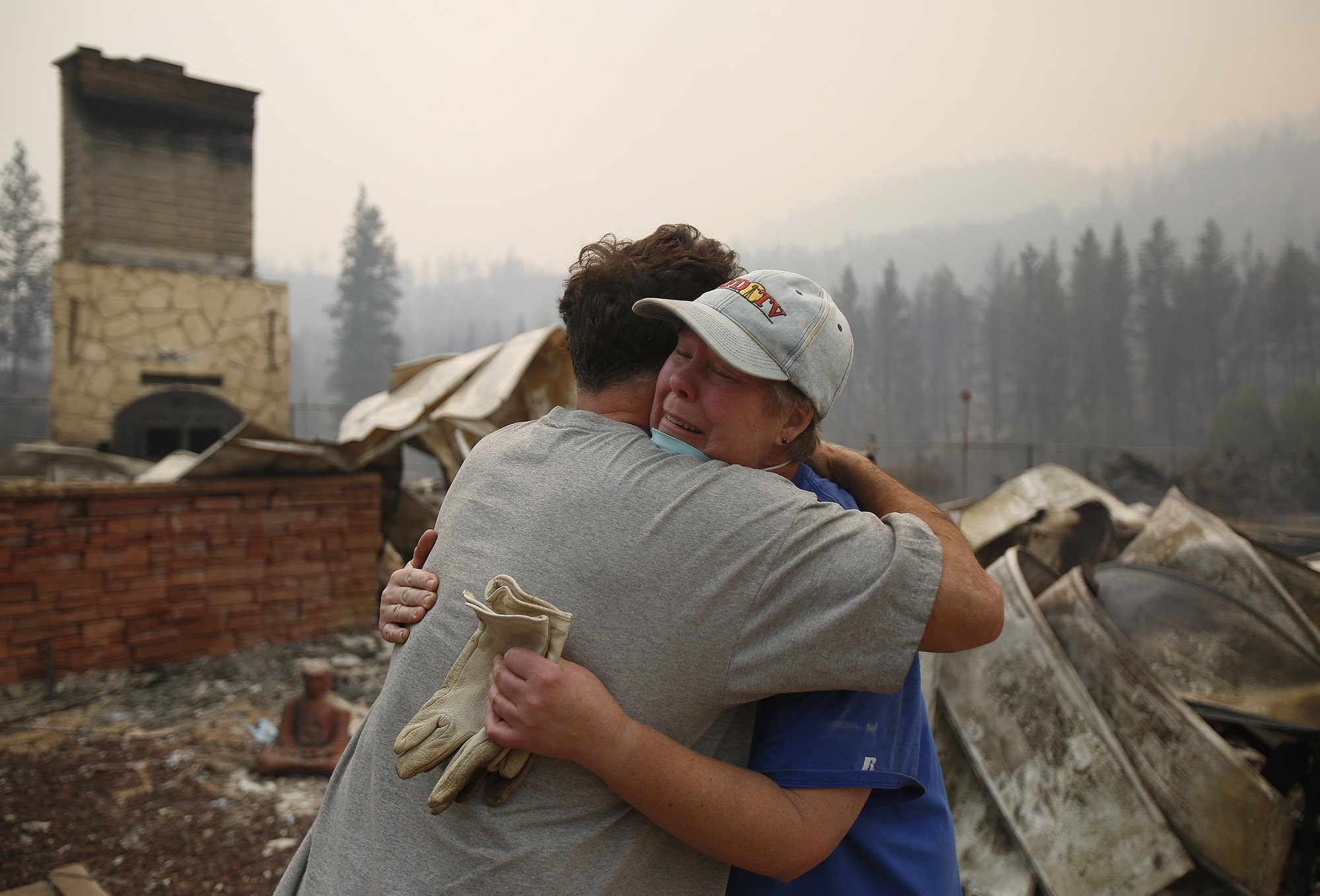 Cindy Aston hugs her neighbor, Todd Quinn, after she lost her childhood home from the firestorm on Saturday, Aug. 15, 2015.