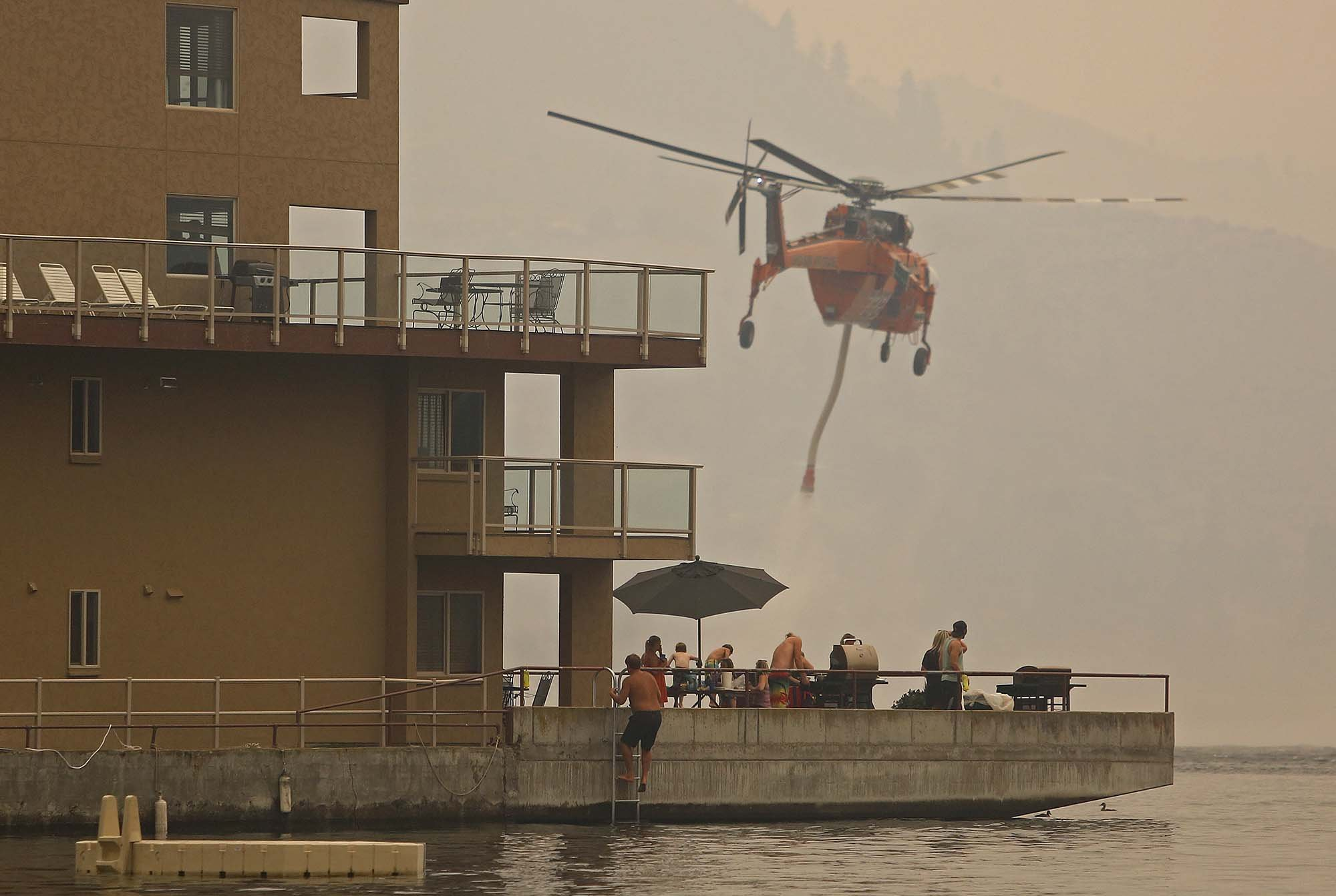 An Erickson Air Crane loads up water on Lake Chelan in as guests at the Grandview On the Lake barbecue, Saturday, Aug. 15, 2015, in Chelan, Wash.