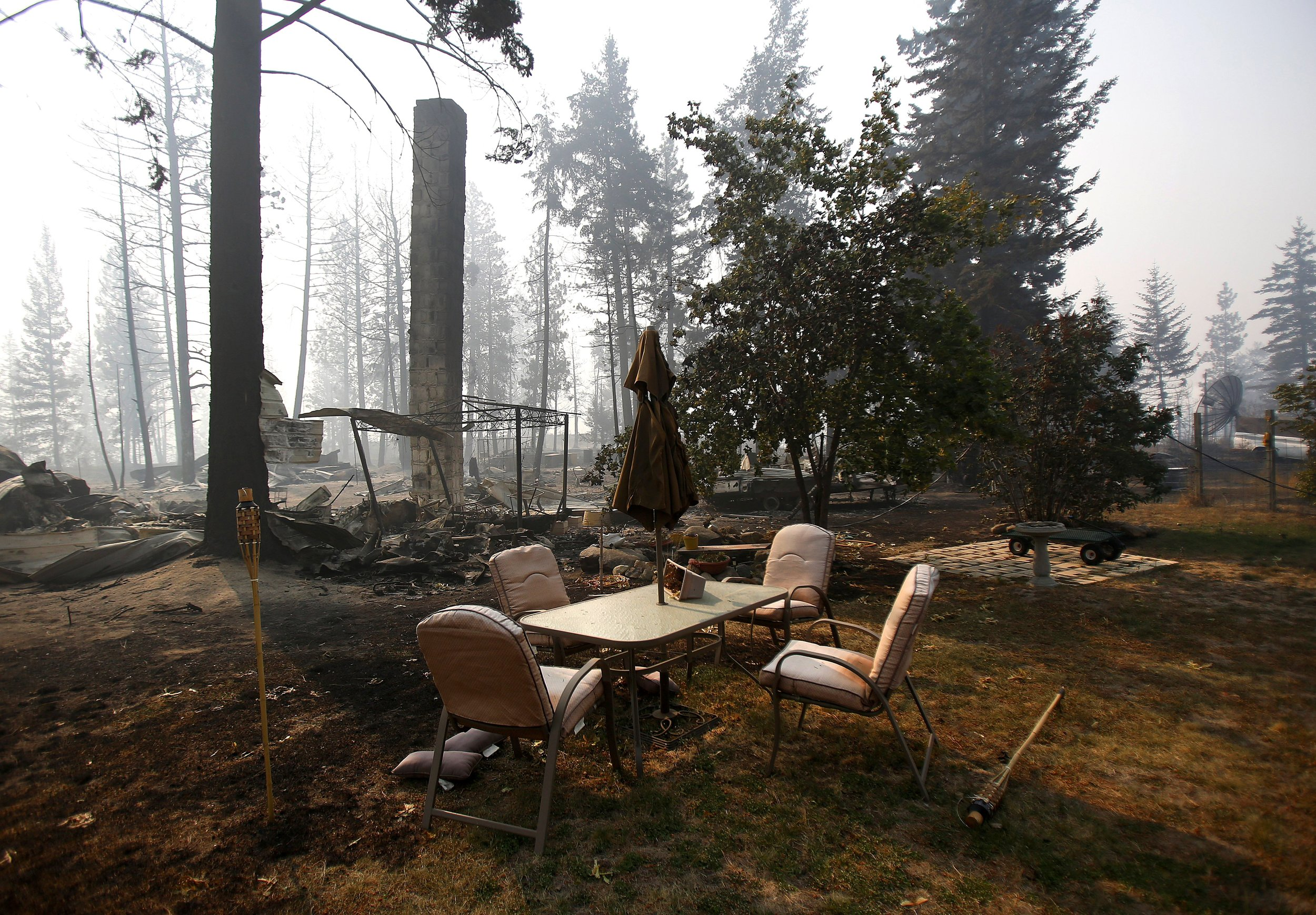 Patio furniture remains relatively untouched after a wildfire swept through the community on White Rock Road, destroying several houses, in Okanogan, Wash., Sunday, Aug. 23, 2015.