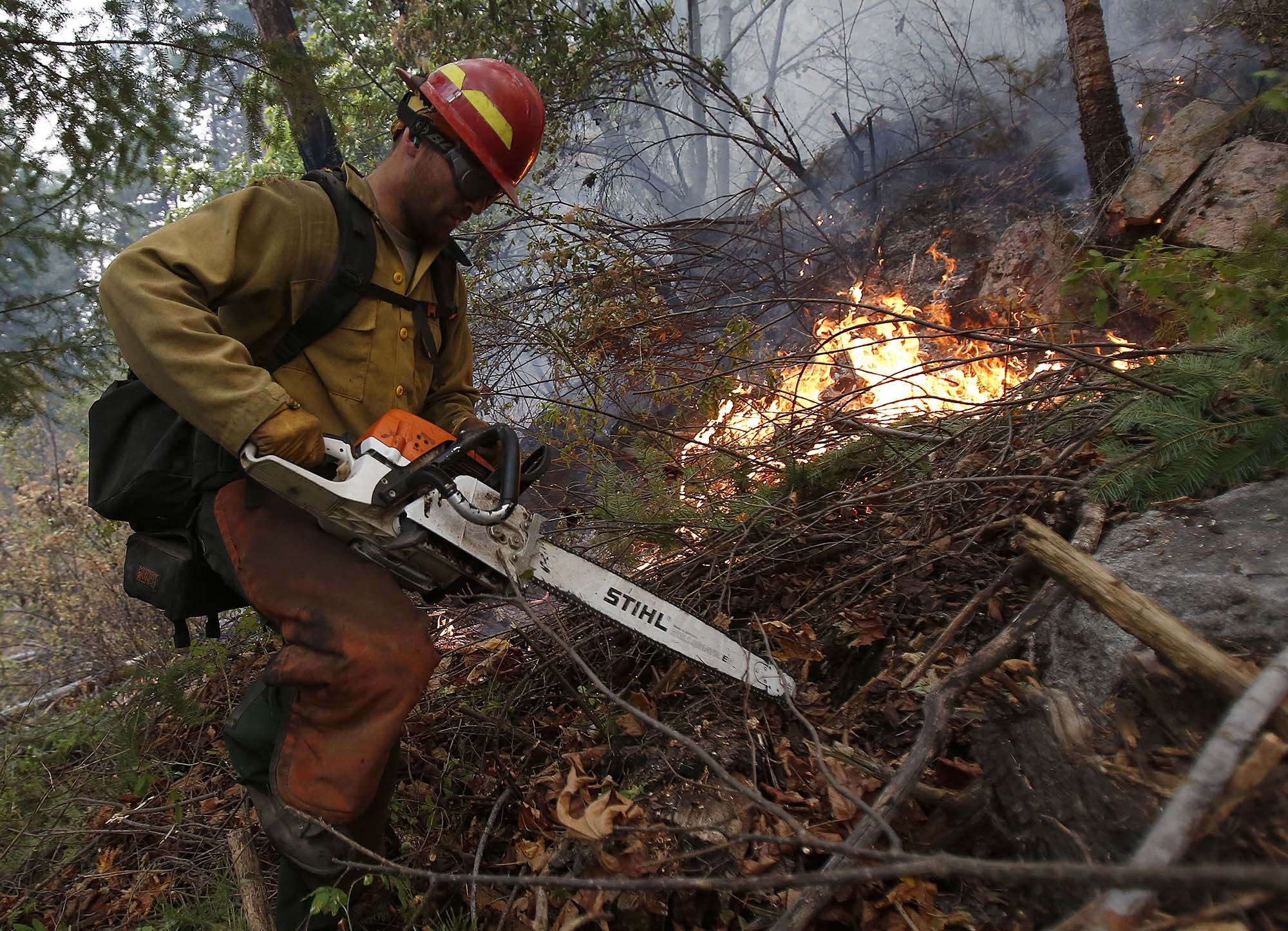 Adam Jordan from Oregon heads back uphill after clearing brush at the First Creek Fire in the Lake Chelan State Park on Sunday, Aug. 16, 2015.