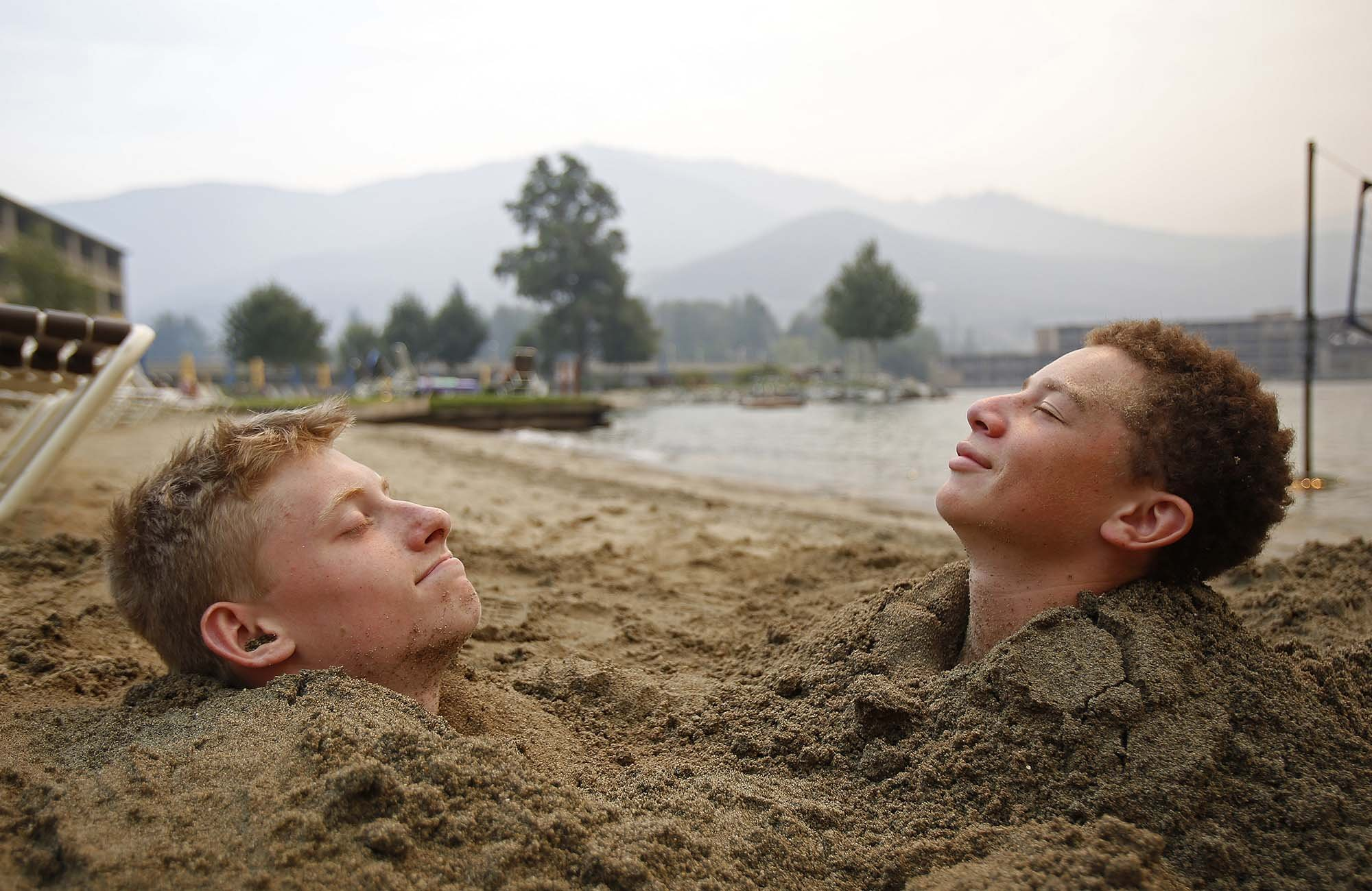 (Left to right) Harrison Noble, 16, and Max Jinjika, 14, relax in the sun on the beach outside of Campbell's Resort at Lake Chelan on Sunday, Aug. 16, 2015.