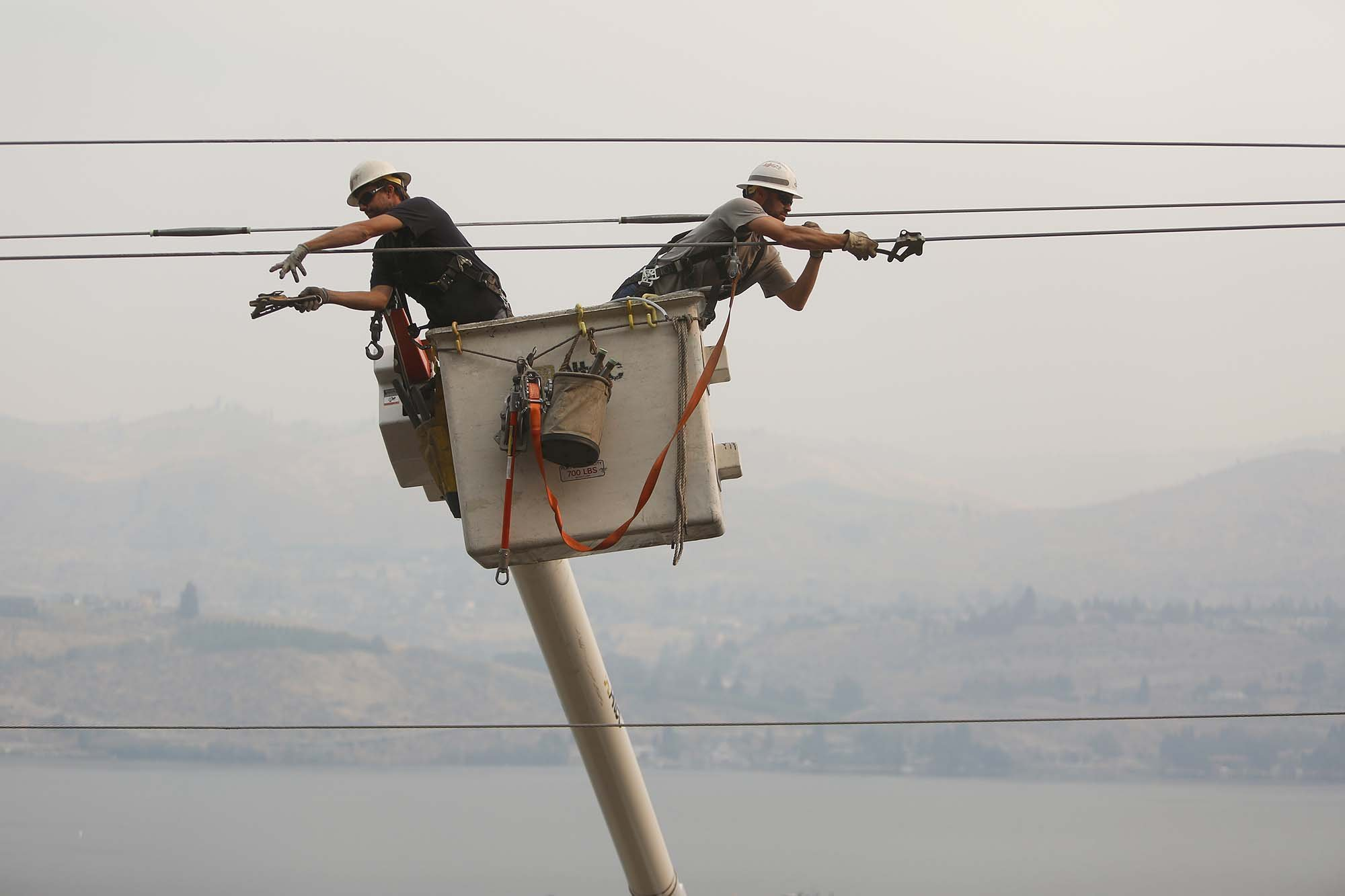 Chelan County PUD linesman Jared Montgomery, left, and Joel Macintosh, right, work on restoring power to the city of Chelan early on Sunday morning as smoke fills the lake, Aug. 16, 2015. Some 9,000 homes were without power last night, and linesman worked through the night to as power is being restored to the city.