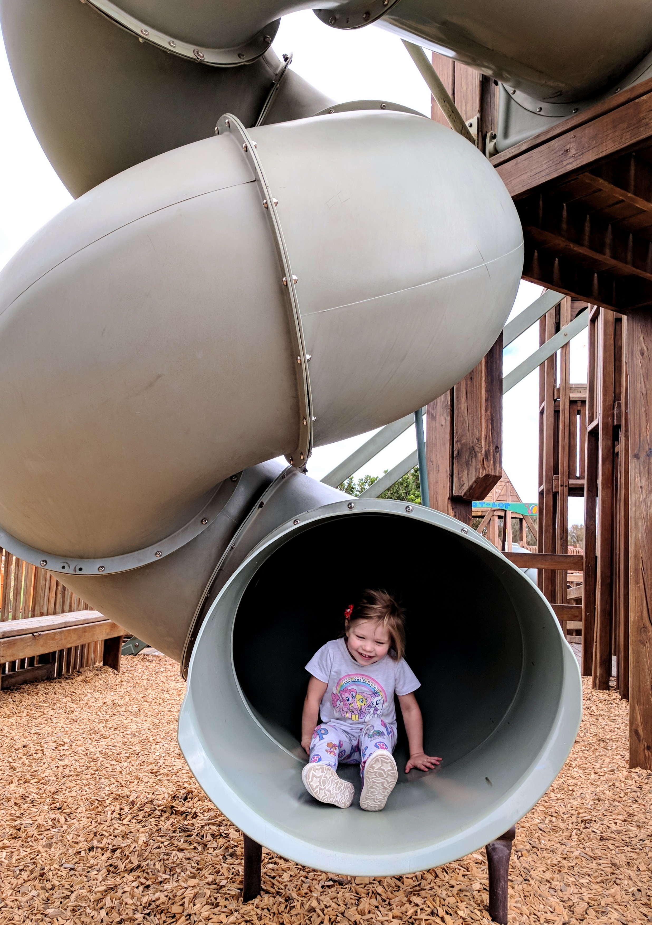 "2. Take a Step Back   Capturing the environment around your children helps to answer the where and the why of the story behind the photo. So rather than always getting up close, take a step back, consider their surrounds and how it might add to the memory. It can be the difference between just a cute smile and a proud three year old who conquered the ""biggest slide ever!"""