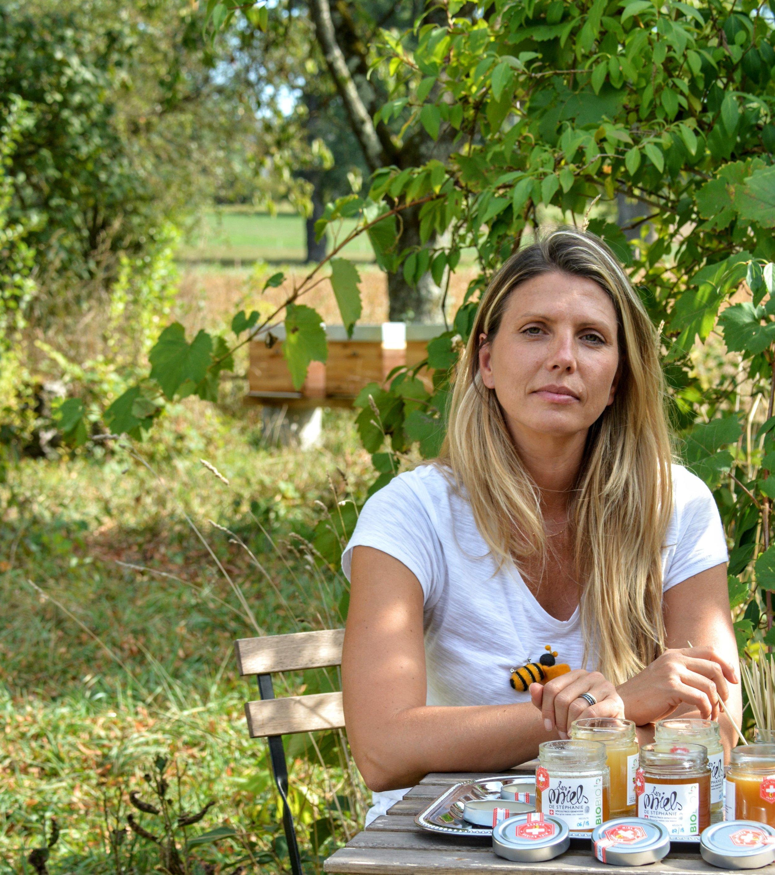 Stéphanie Vuadens - Apicultrice genevoise, Stéphanie est maman de deux enfants. Plus qu'un métier, une véritable mission : protéger nos abeilles, et préserver notre écosystème pour la beauté et la biodiversité de nos campagnes.Proche de la nature, pour Stéphanie, l'apiculture est aussi et surtout, une mission, une transmission et un retour au « bien manger ». On dit souvent que les abeilles sont les sentinelles de la nature, pour Stéphanie, faire partie de leurs gardiens est un privilège.