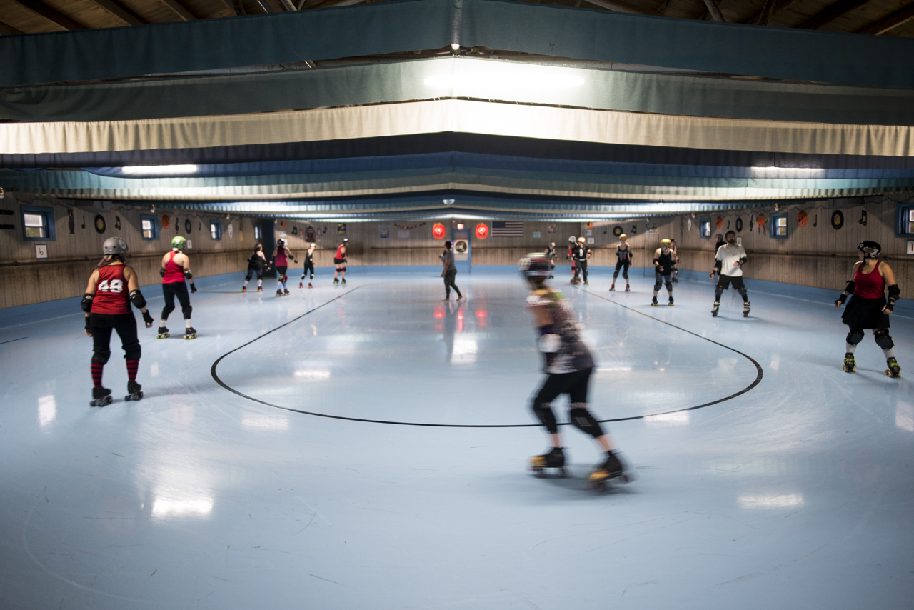 Members of the Appalachian Hellbetties skate laps to warm up for practice at the Dow Roller Arena in Athens Ohio.