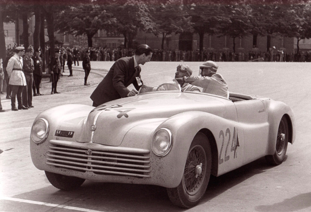 Photo:  Detail during the 1948 Mille Miglia. Official talking with driver Spartaco Graziani. Source: Archivio Foto Locchi Firenze, archival number 1948_L402-32. www.fotolocchi.it