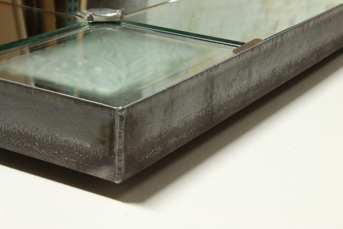 A raw welded steel float frame hosting an oversize Art Deco mirror. For added stability, a wood panel back with engaged cleat was installed. Backing and a wall mounting wedge for secure installation.