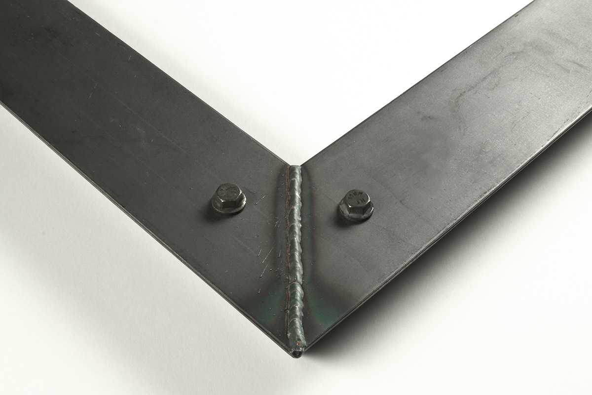 """Detail of a 2.5"""" wide molding steel frame with bolt decoration"""