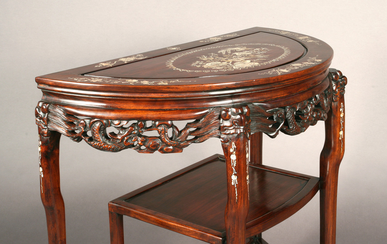 Chinese Rosewood Mother-of-Pearl Inlay Console Table with open carvings of dragons adorning the apron edge
