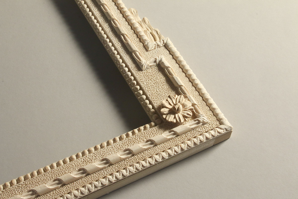 Hand carved corner of a decorative trumeau frame design. Note the asymmetric corner and the tactile quality that hand carving provides for the beaded, lamb's tongue ribbon ornamentation.