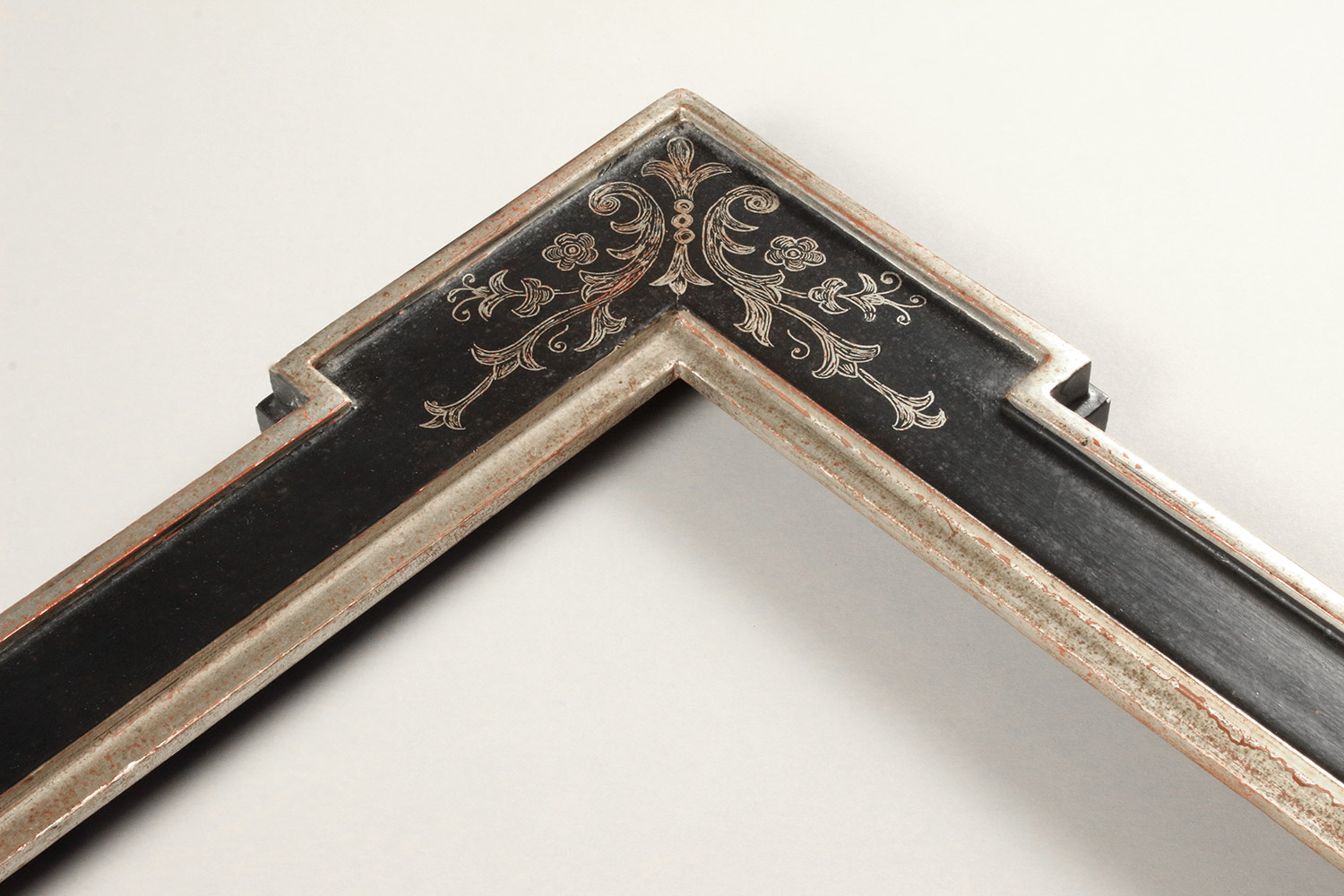 A white gilded frame with a black painted panel with a corner sgraffito design.
