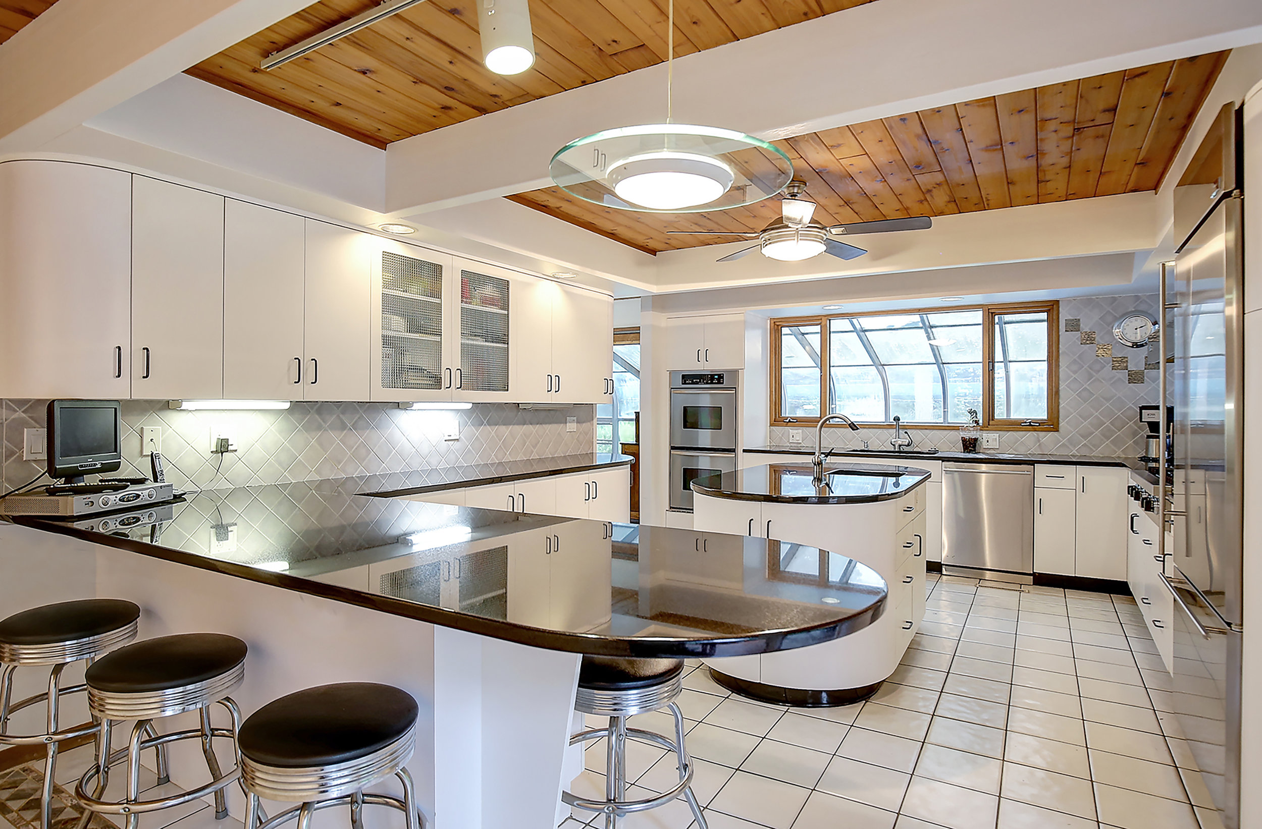 4 The sleek contemporary kitchen offers a breakfast bar and extensive prep space IMG_6000_1_2.jpg