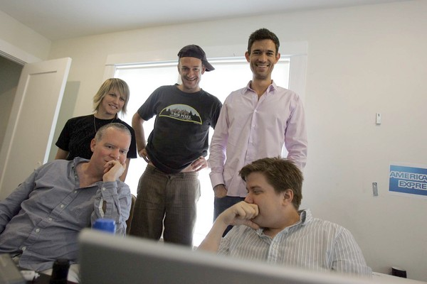 BRAINSTORMING: FunnyorDie head of production Mike Farah, standing at right, with cap-wearing writer-actor Seth Morris and other staffers. (Photo courtesy of Gary Friedman, Los Angeles Times)