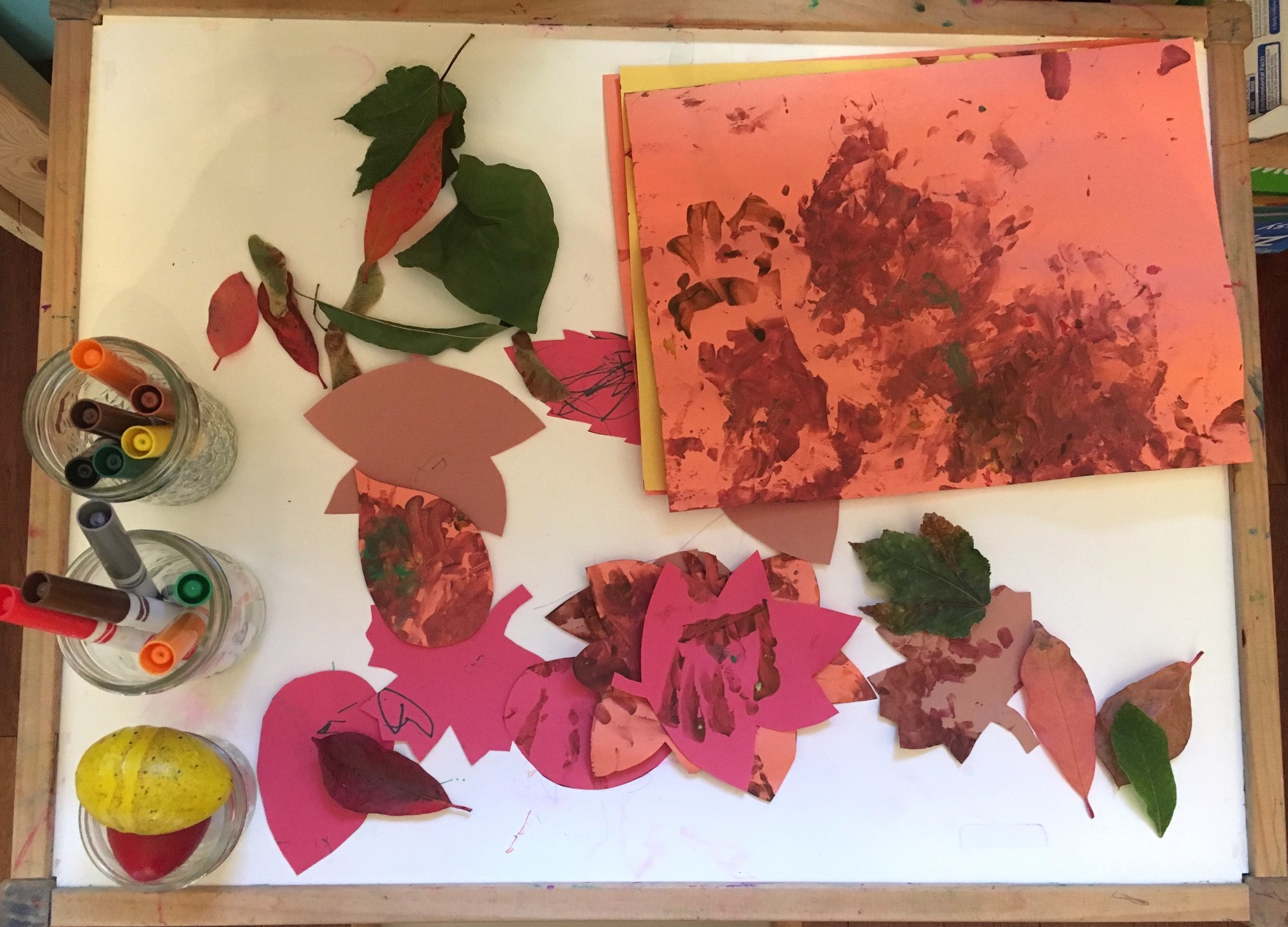 Image: an art table with fall leaves, markers, crayons and construction paper
