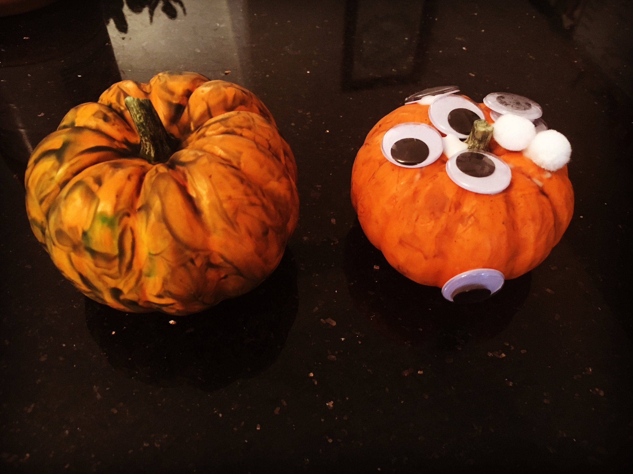 Image: two mini pumpkins decorated by toddlers