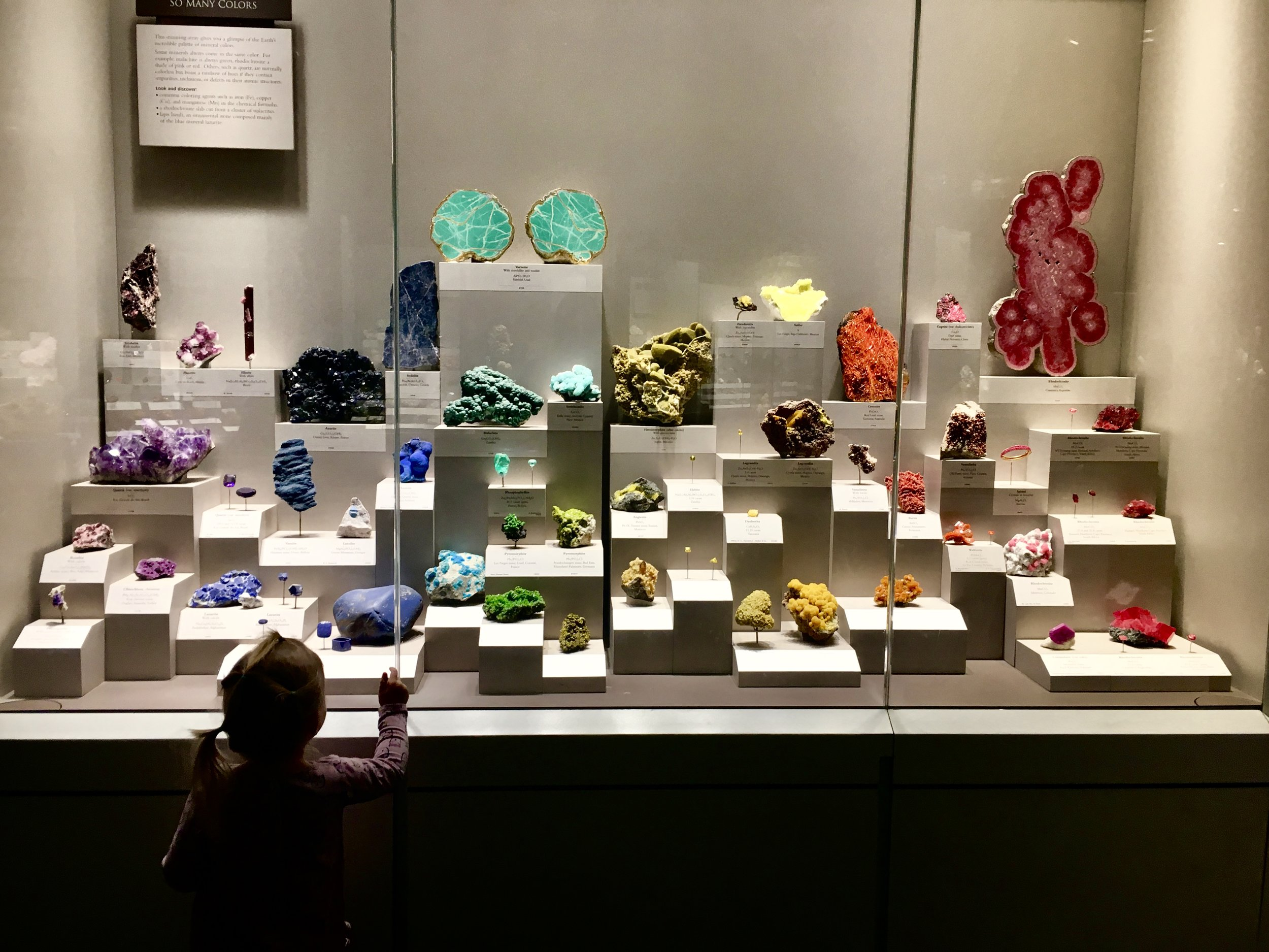 Image: A toddler in front of a display of colorful rocks and minerals