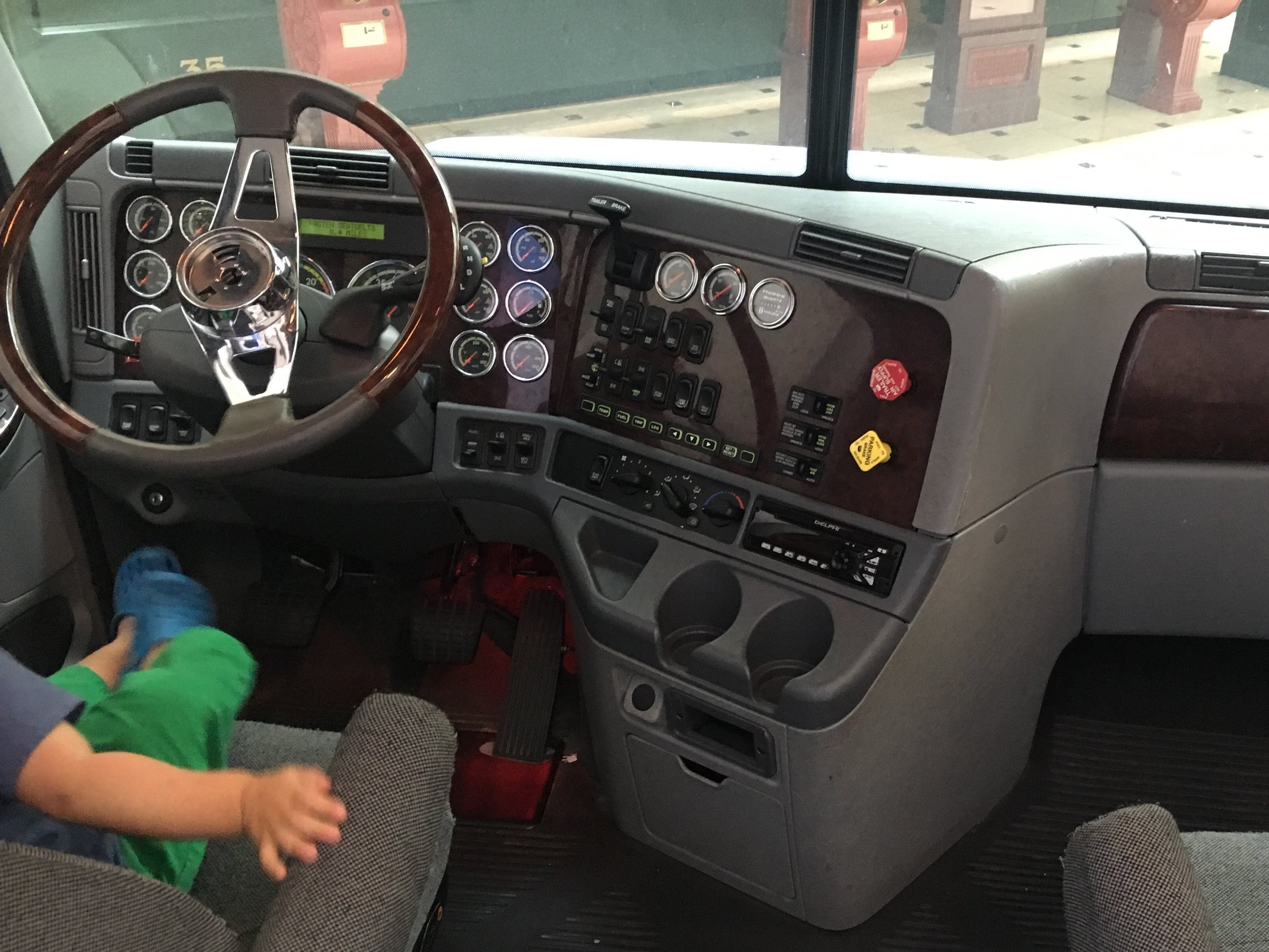 Image: a toddler driving a truck at the US Postal Museum