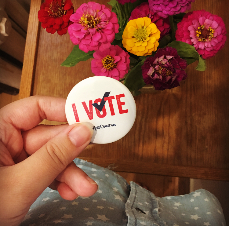 "Image: a hand holding a pin that says ""I Vote,"" with flowers in the background."