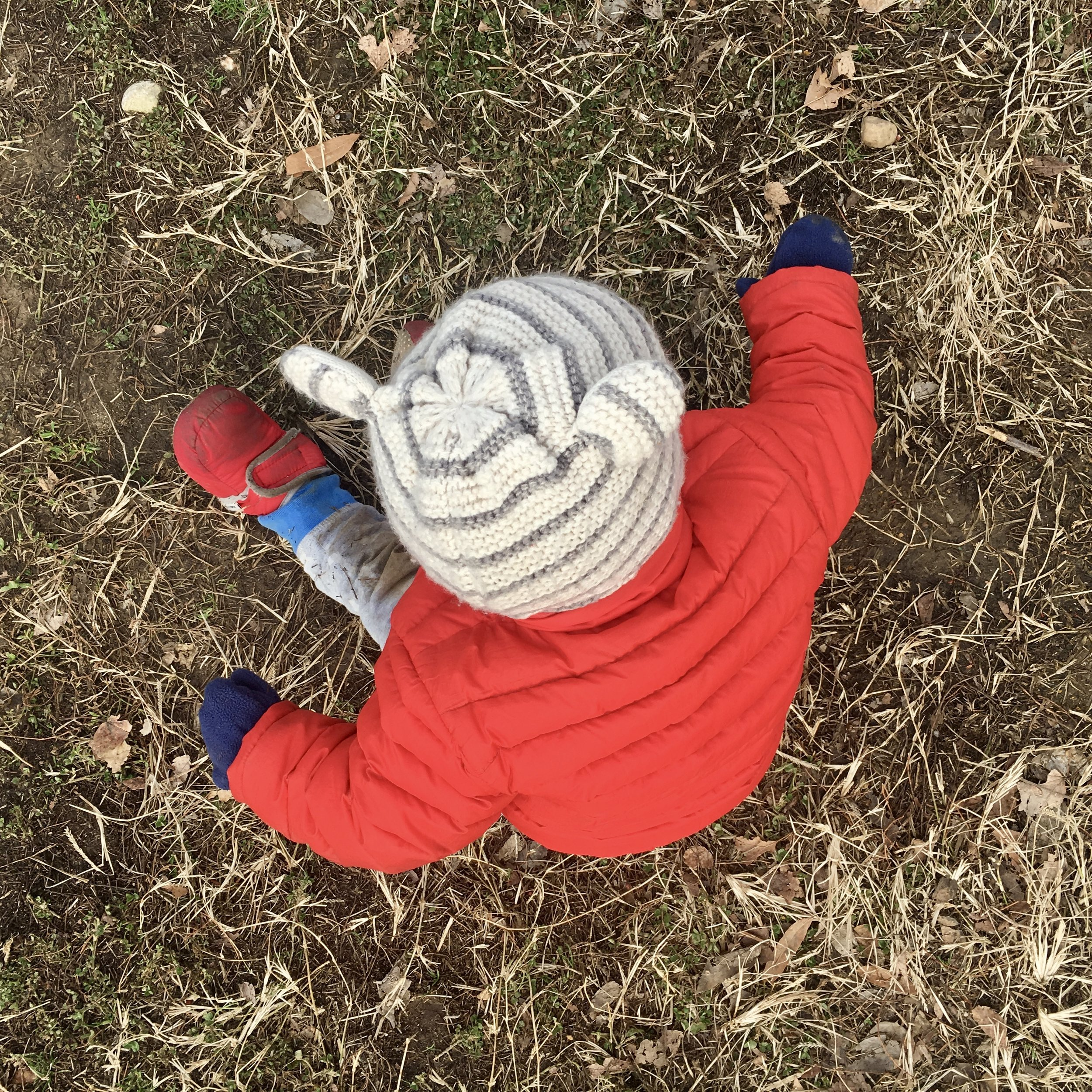 Image: a baby in winter clothes sits in the dirt and dead grass.