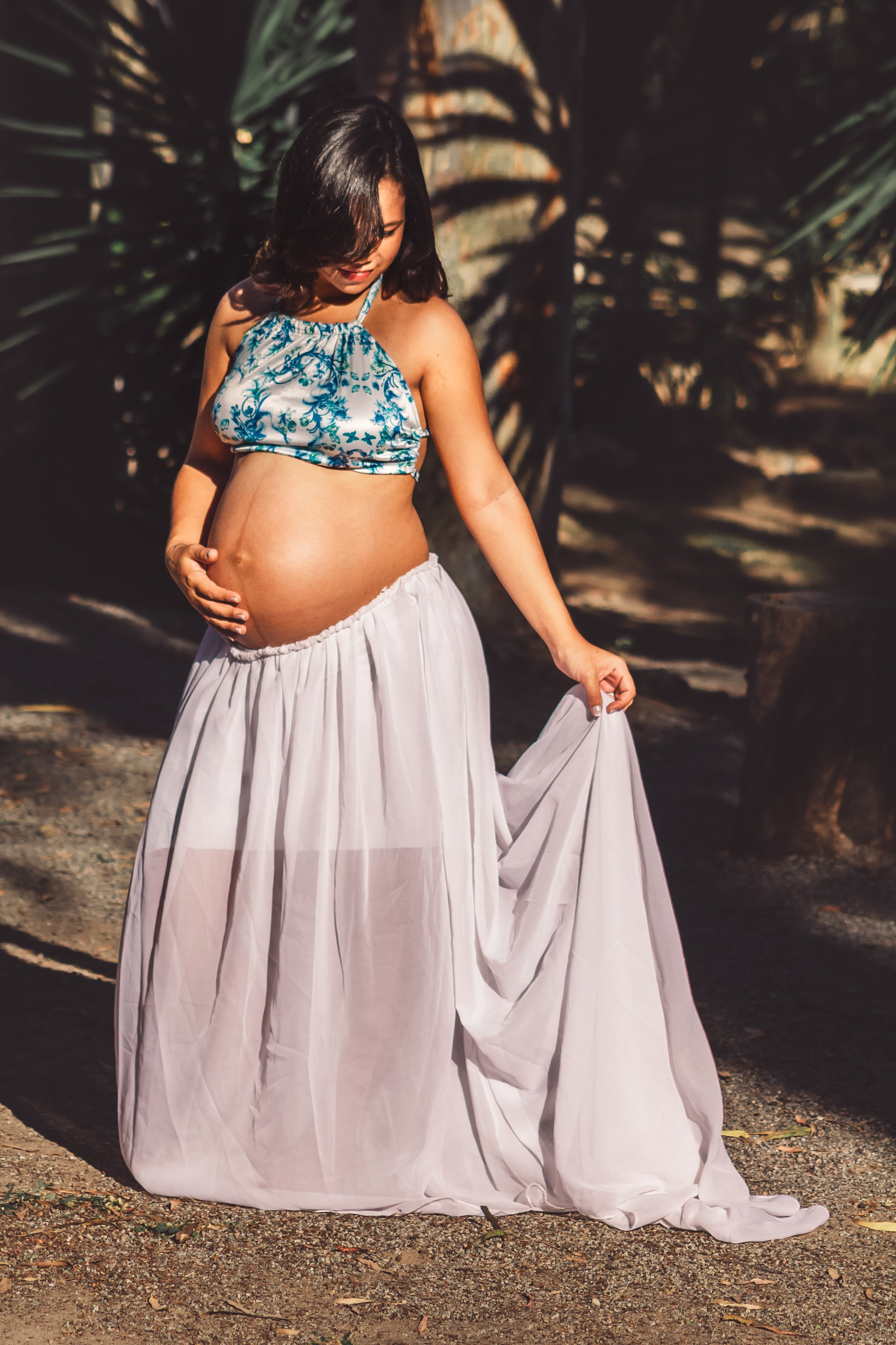 Image: a pregnant woman in a bra top and flowing skirt. Image credit: Pexels