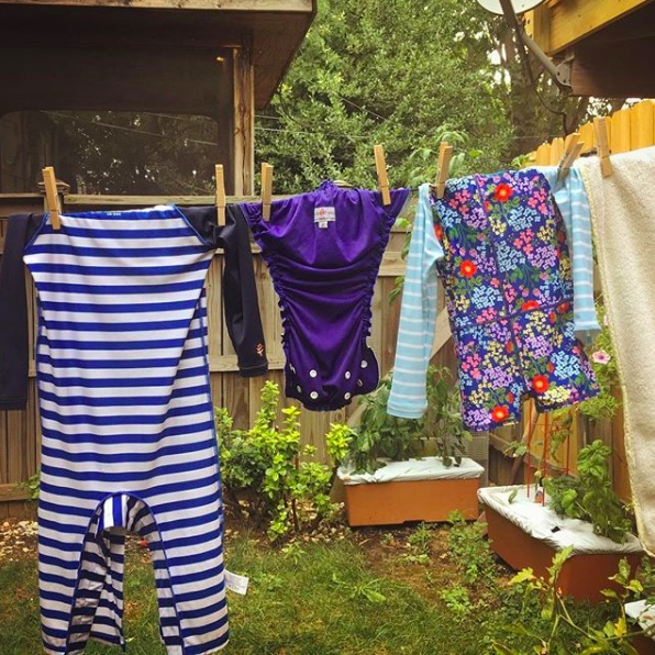 Image: toddler clothes and cloth diapers hang on a backyard clothesline. Image copyright Elisabeth Caron