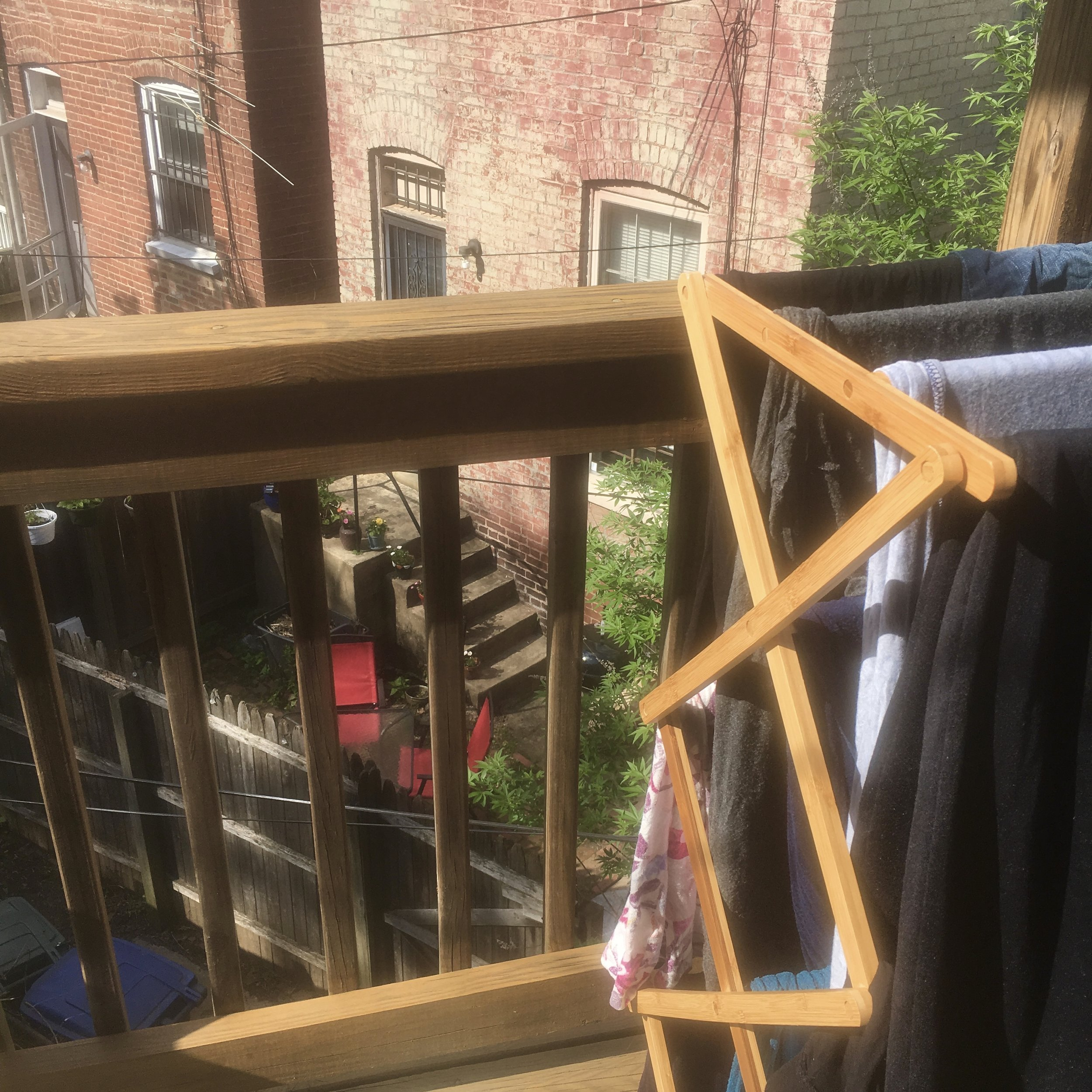 Image: A view of rowhouse back alleys and balconies with a rack of drying clothes on a balcony. Image copyright Elisabeth Caron