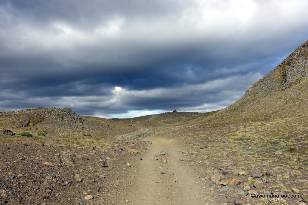Hiking solo the dramatic Laugavegur trail in Iceland- through black sands, colorful rocks, lava fields, ice bridges, and geysers. See why you should put this marvelous trail on your bucket list @ AWOMANAFOOT.COM! | Hiking in Europe | Adventures in #Iceland |#Destinations for solo female hikers | Hiking and camping in Iceland | female #solo #hiking | bucket list #trail | geysers | glacier | #mountains | #Landmannalaugar | #Thorsmork |
