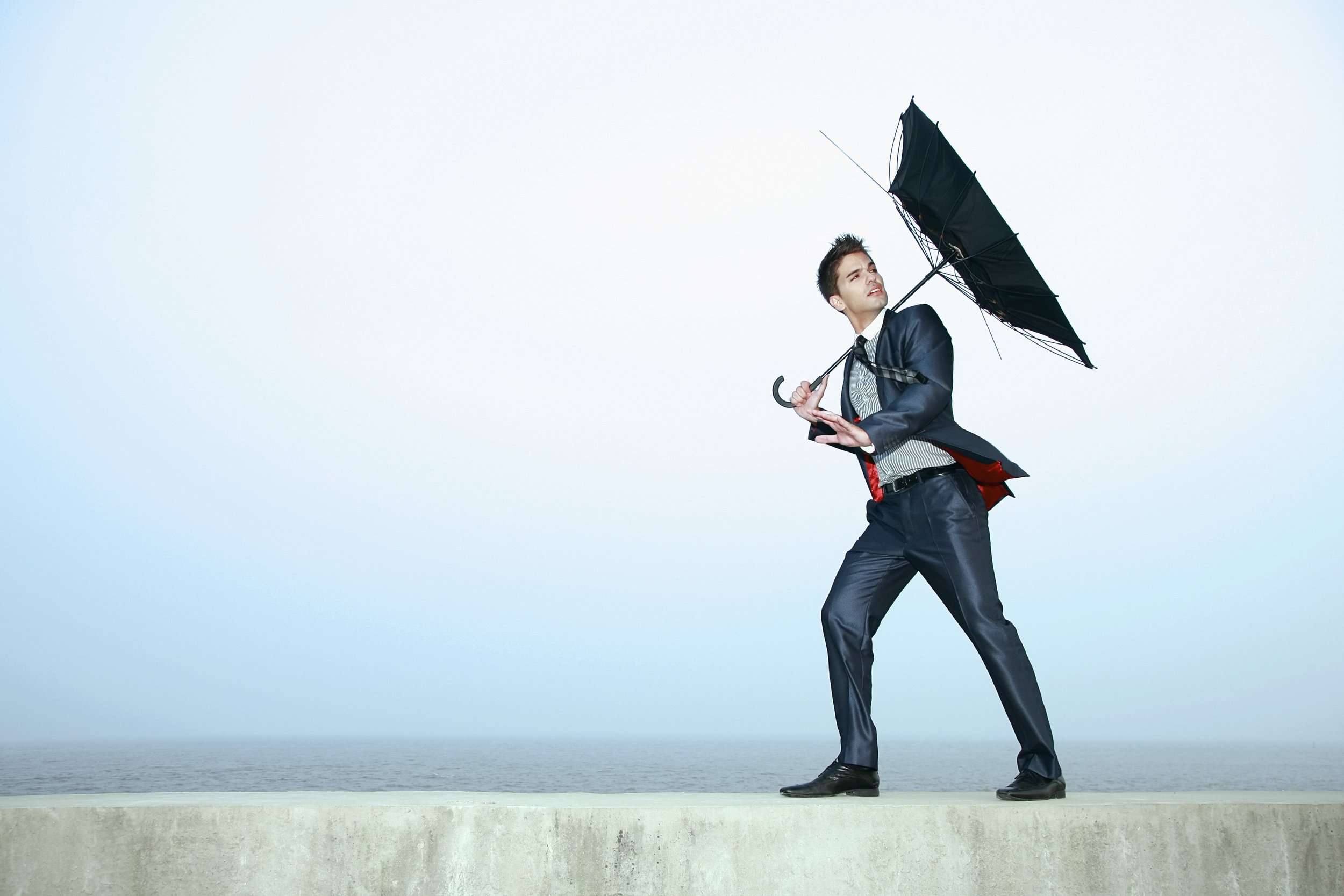 Man struggles with an inside-out umbrella in the wind.