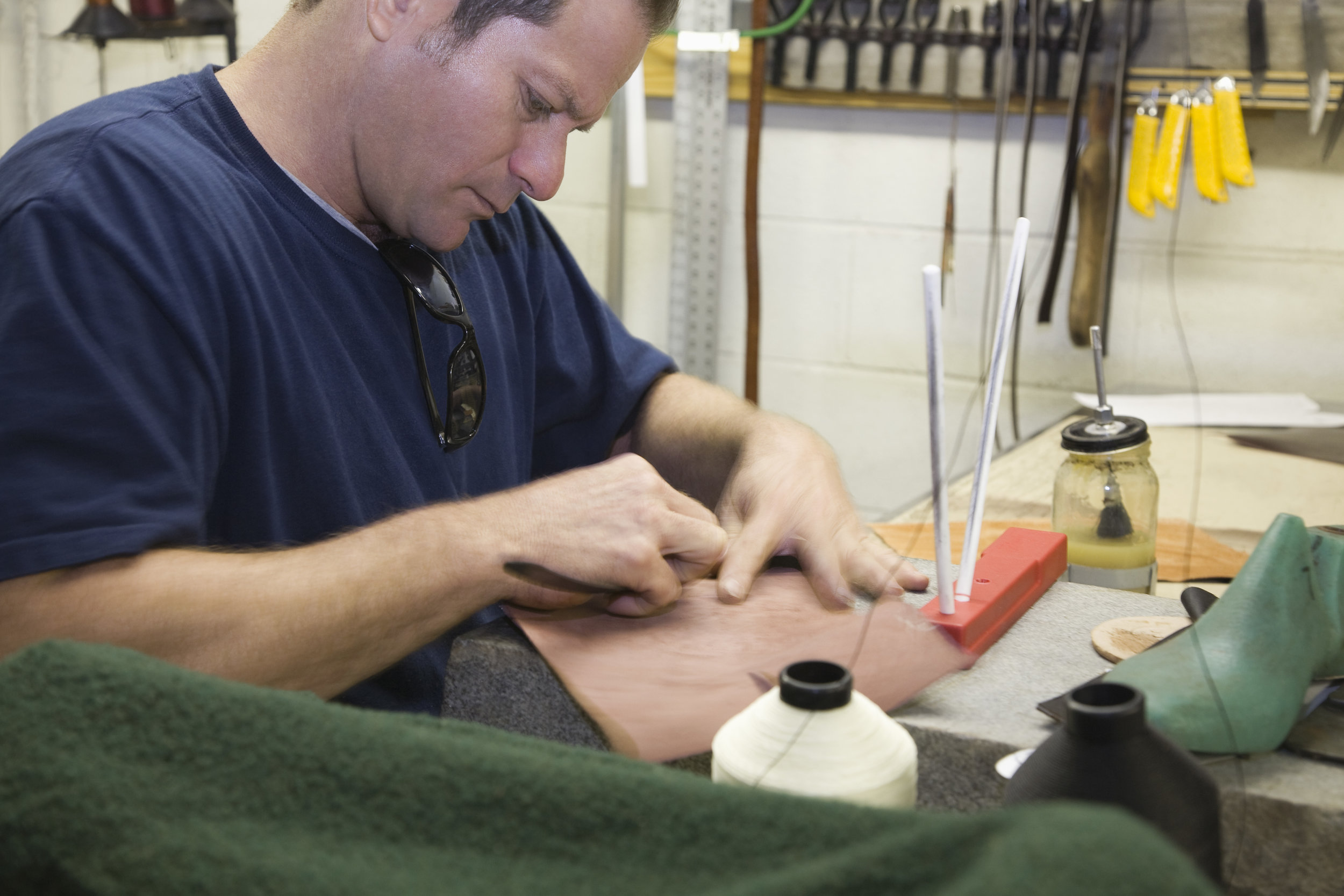 White male works raw leather with hand tools in a traditional boot making shop.