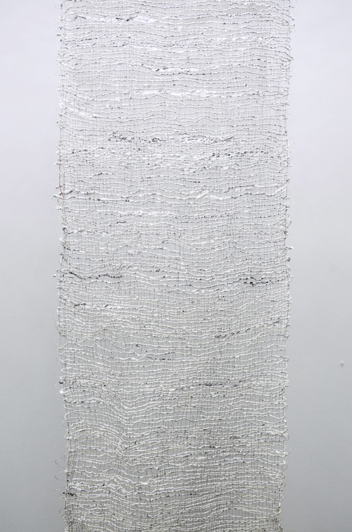 Jessica Wildman,  moral fiber , 2015. Hand spun confessions and intentions written by the public with india ink on sumi paper, woven on site into a linen warp with wire and brass.
