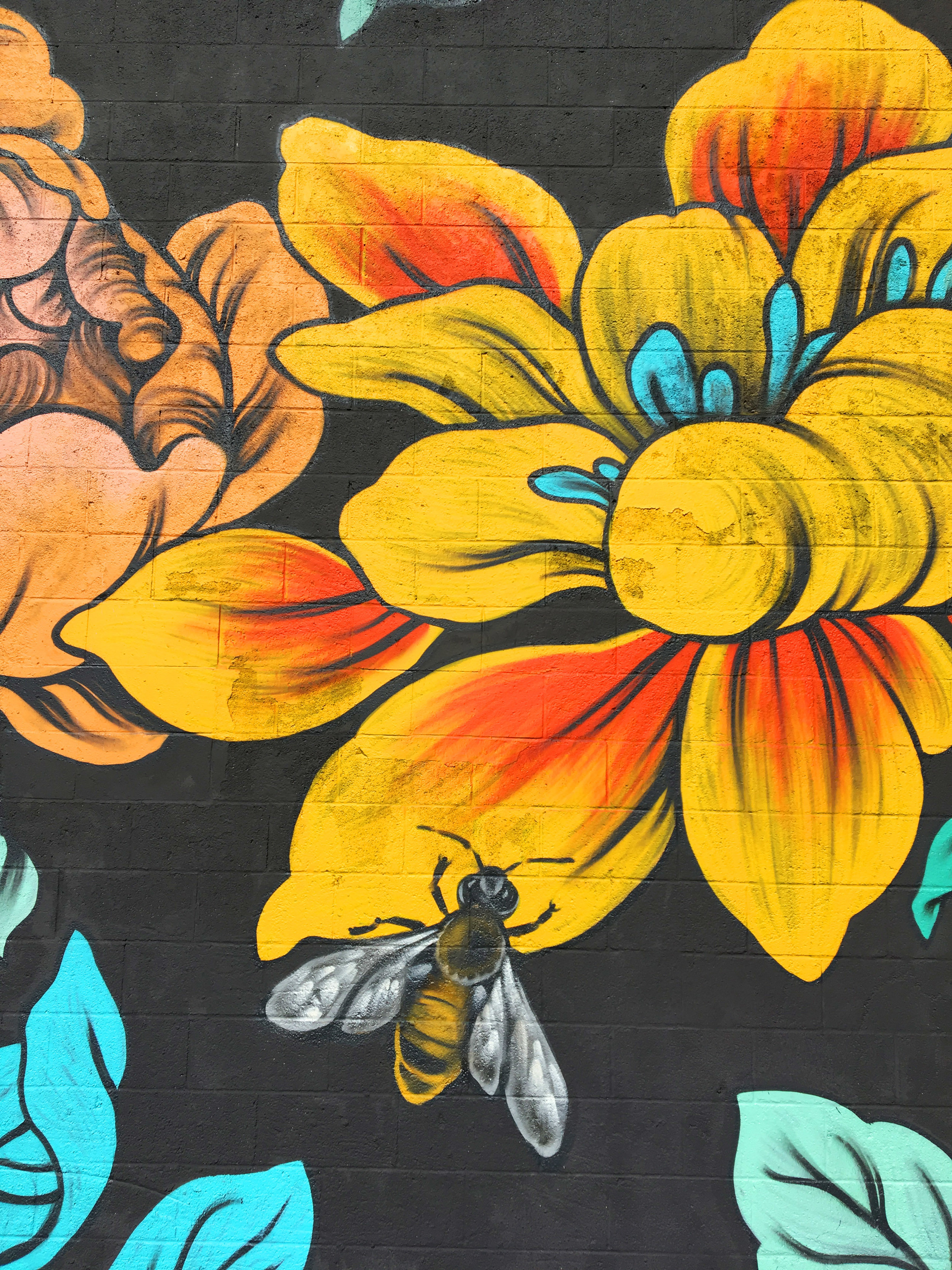 Detail of bee on flower for Ouizi mural on exterior of Grand Rapids Ballet