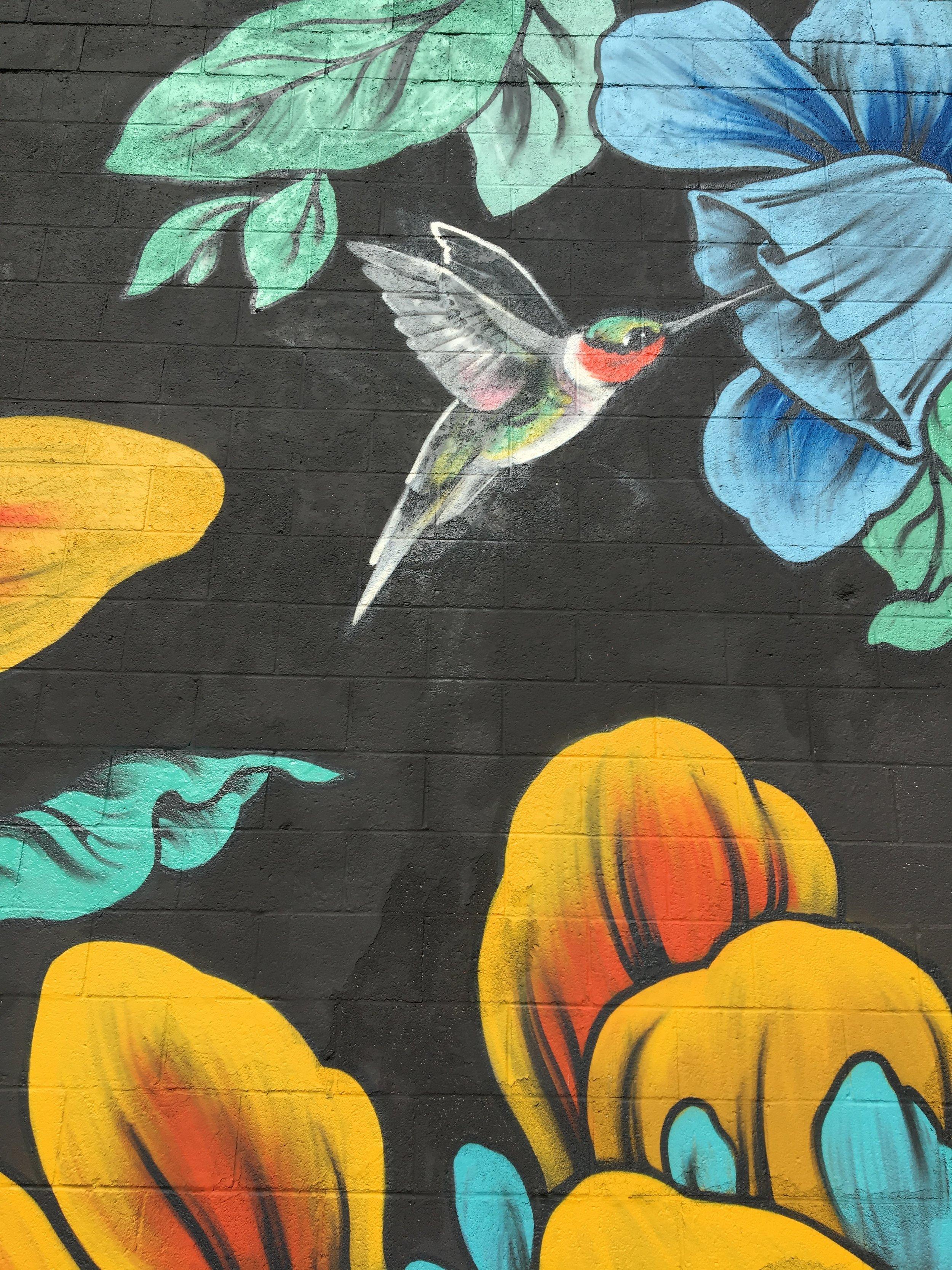Detail of hummingbird in flowers in Ouizi floral mural on Grand Rapids Ballet