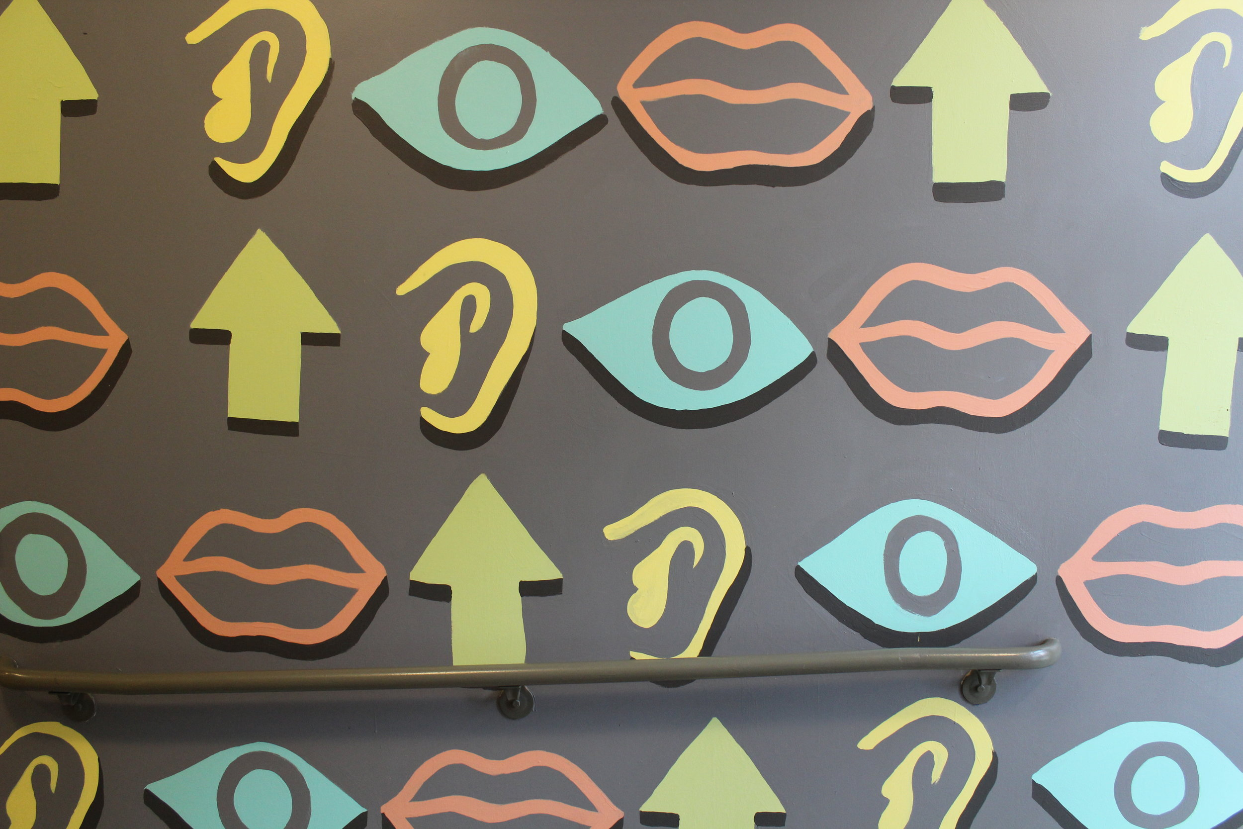 Detail of eyes, lips, ears, and arrow pattern in Artworks mural