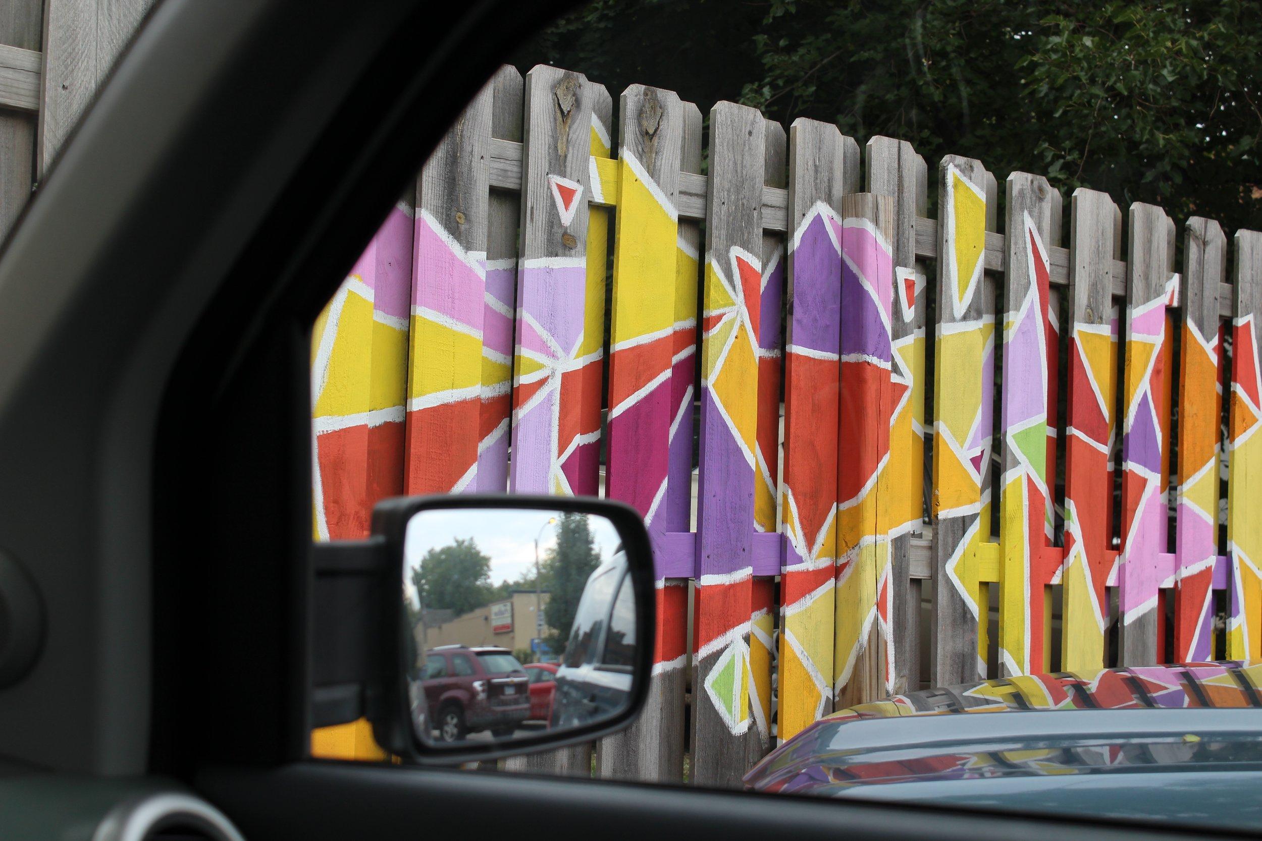 Detail through car window of mural on fence