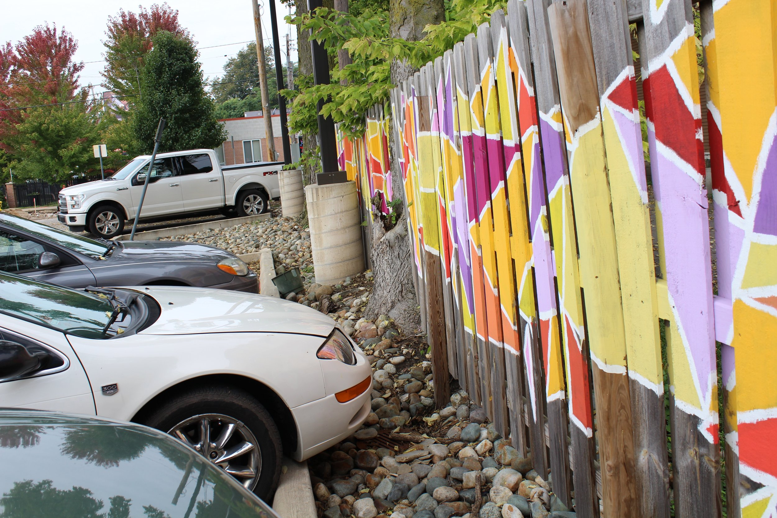 Geometric abstract mural on pavement and fence of Fulton St. parking lot