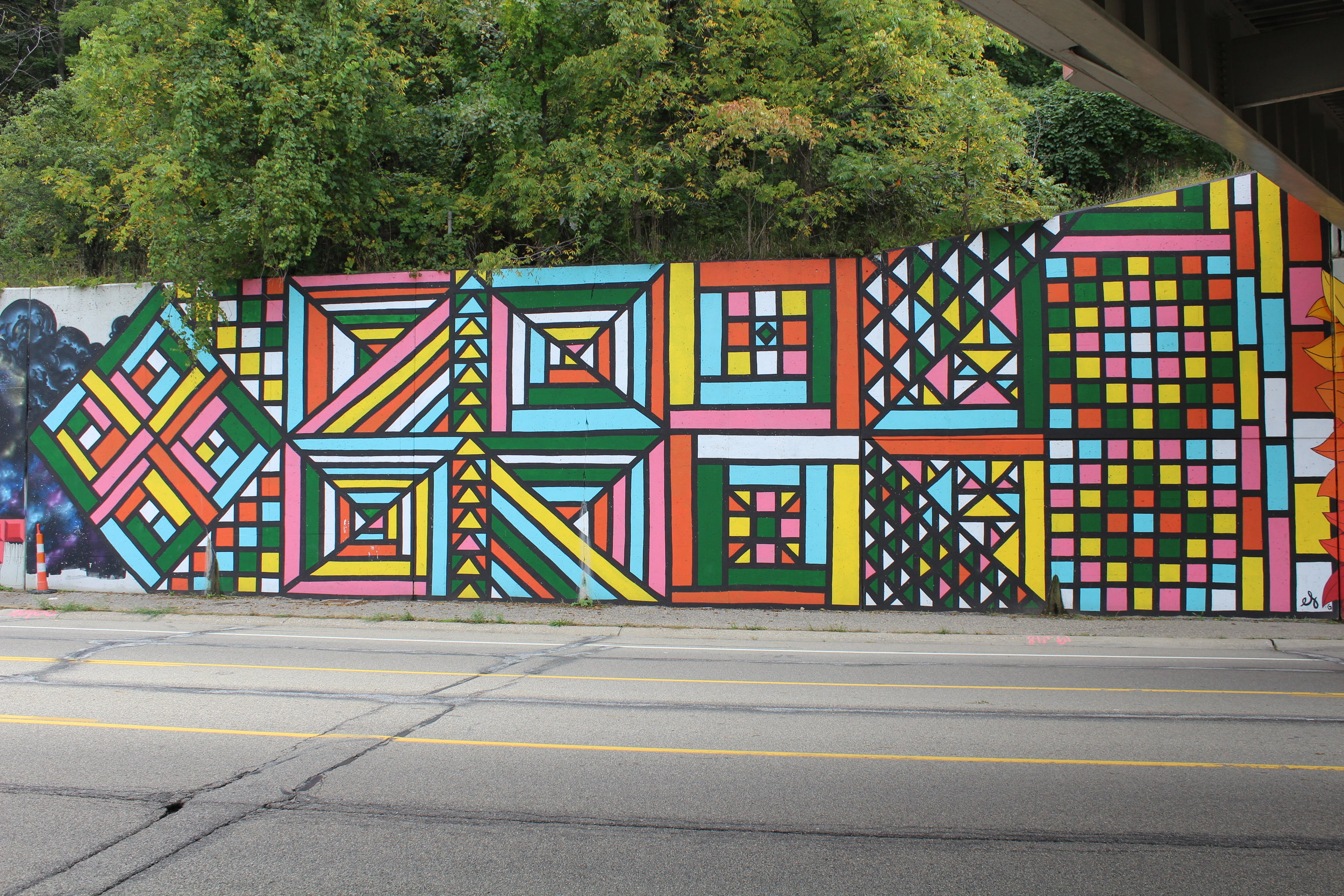 Geometric quilt mural on retaining wall of I-196