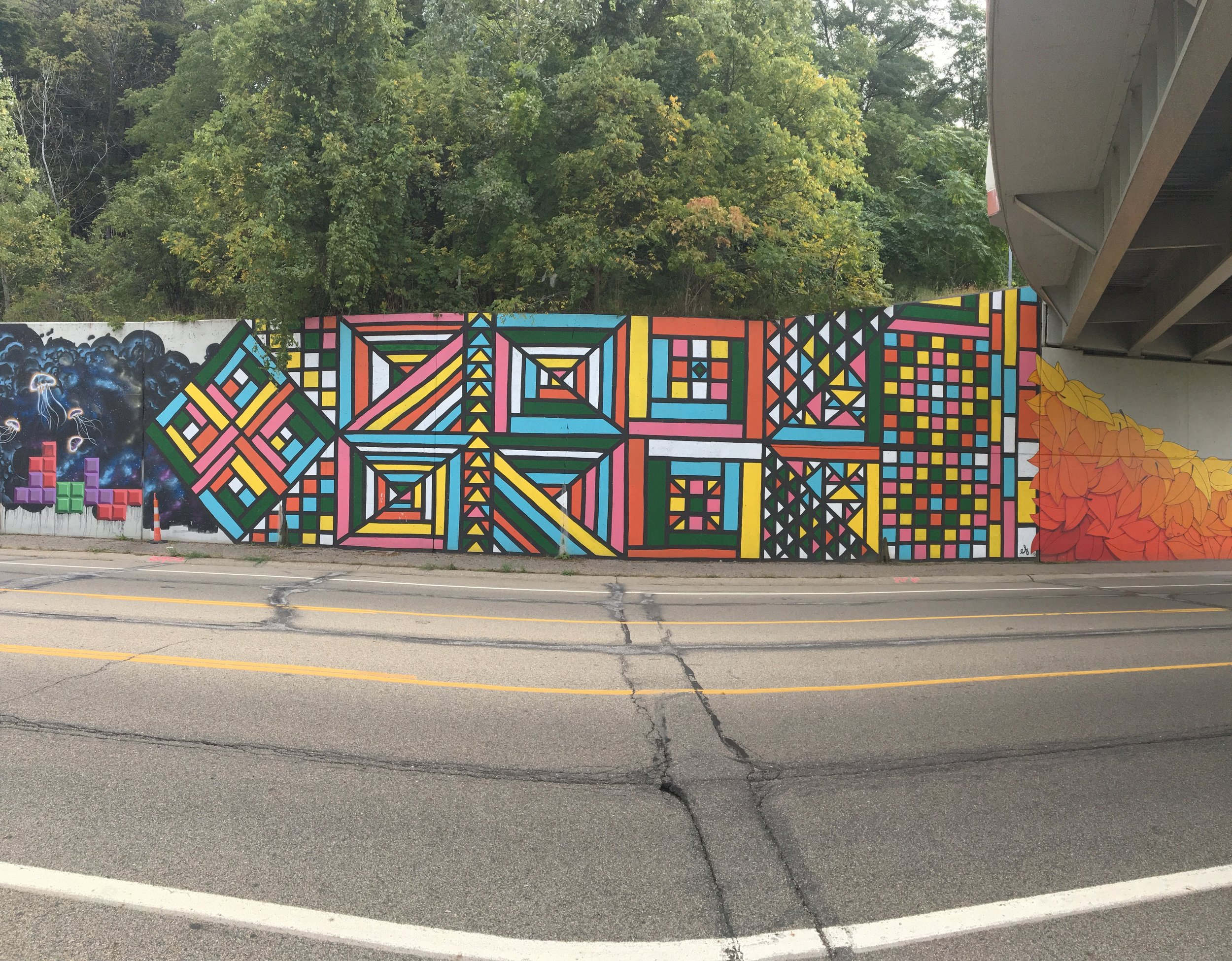 Geometric quilt mural on retaining wall of I-196 (full view)