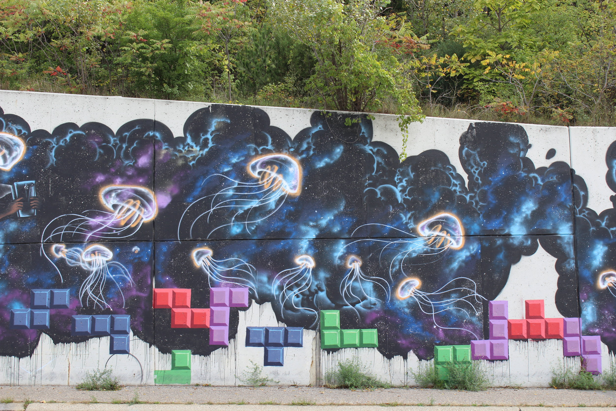Space inspired mural on retaining wall of I-196