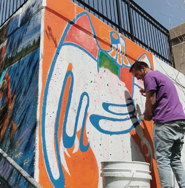 Alan Campo working on West Side mural