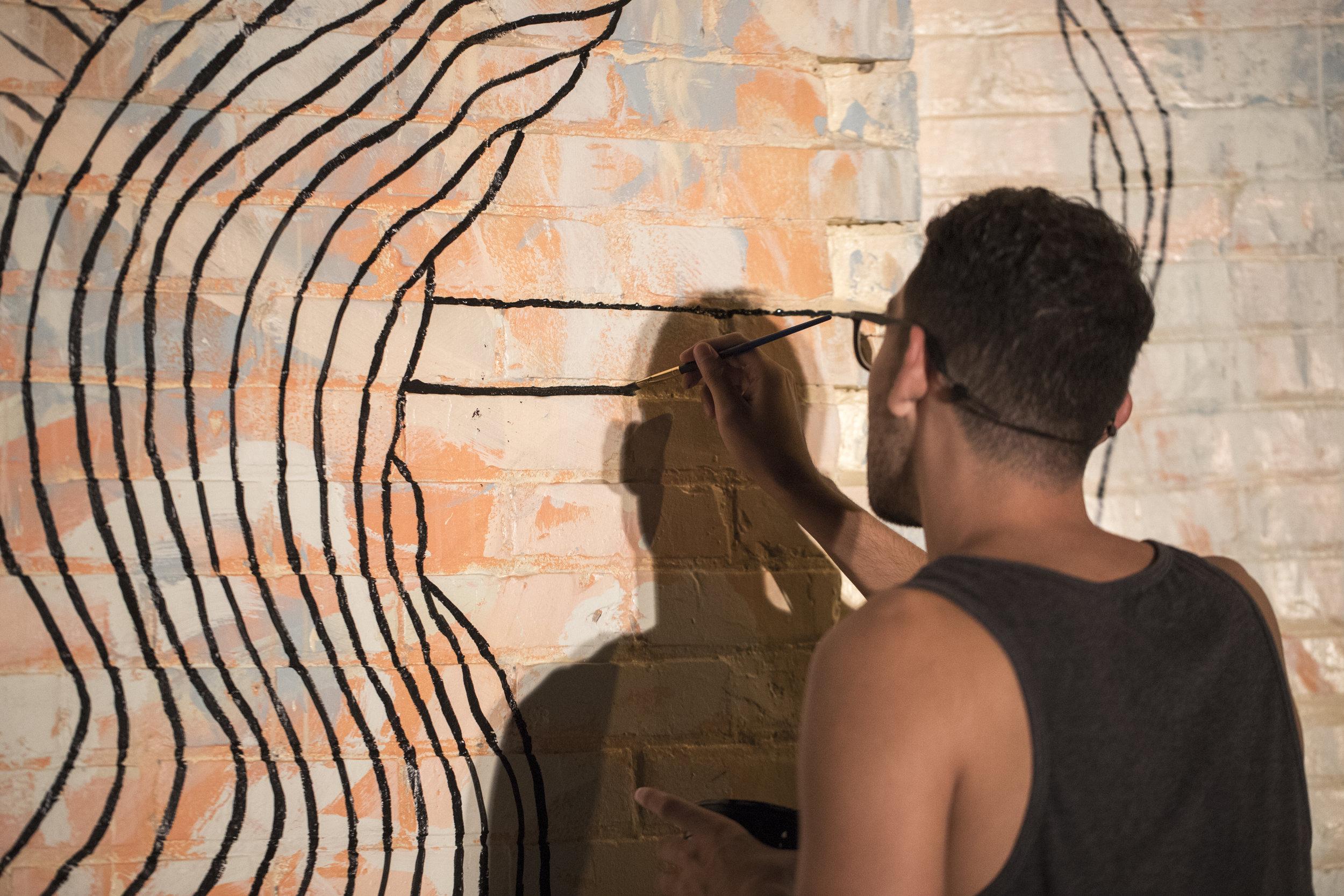 Colby Roanhorse working on Creston mural
