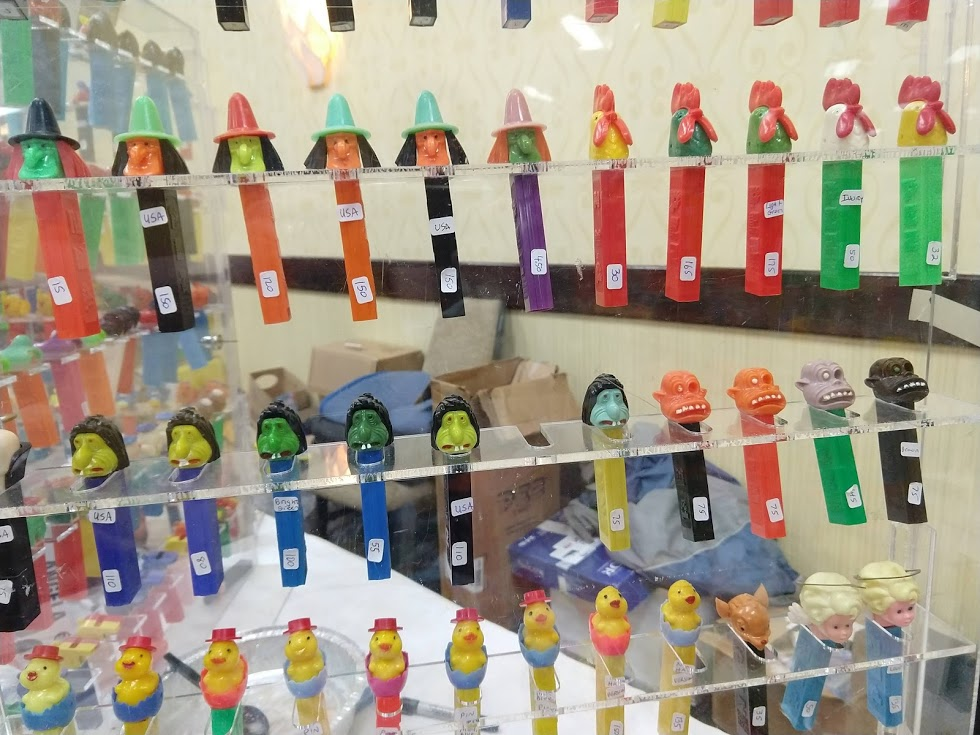 A sampling of PEZ dispensers on display. Yes, those are prices. The small numbers (2.6, 3.4, etc.) indicate the patent number on the dispenser's stem. Lower numbers often mean older dispensers.