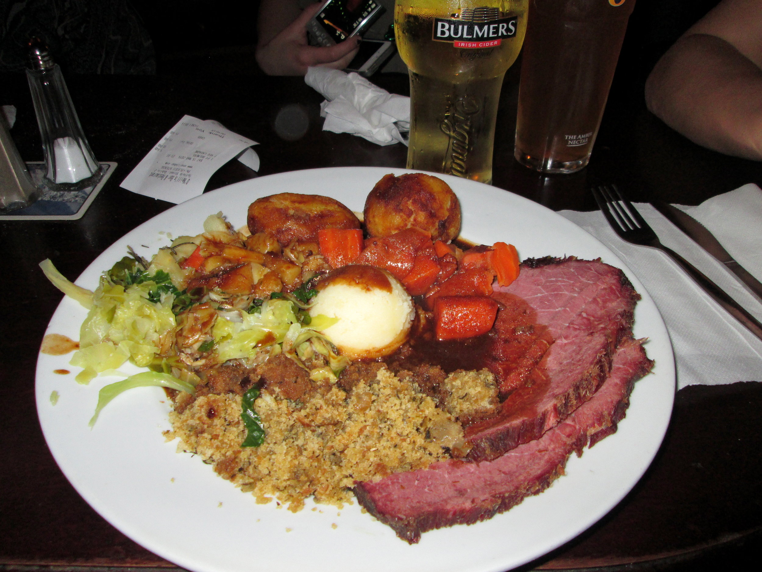 Traditional Corned Beef with stuffing, greens and mashed potatoes.